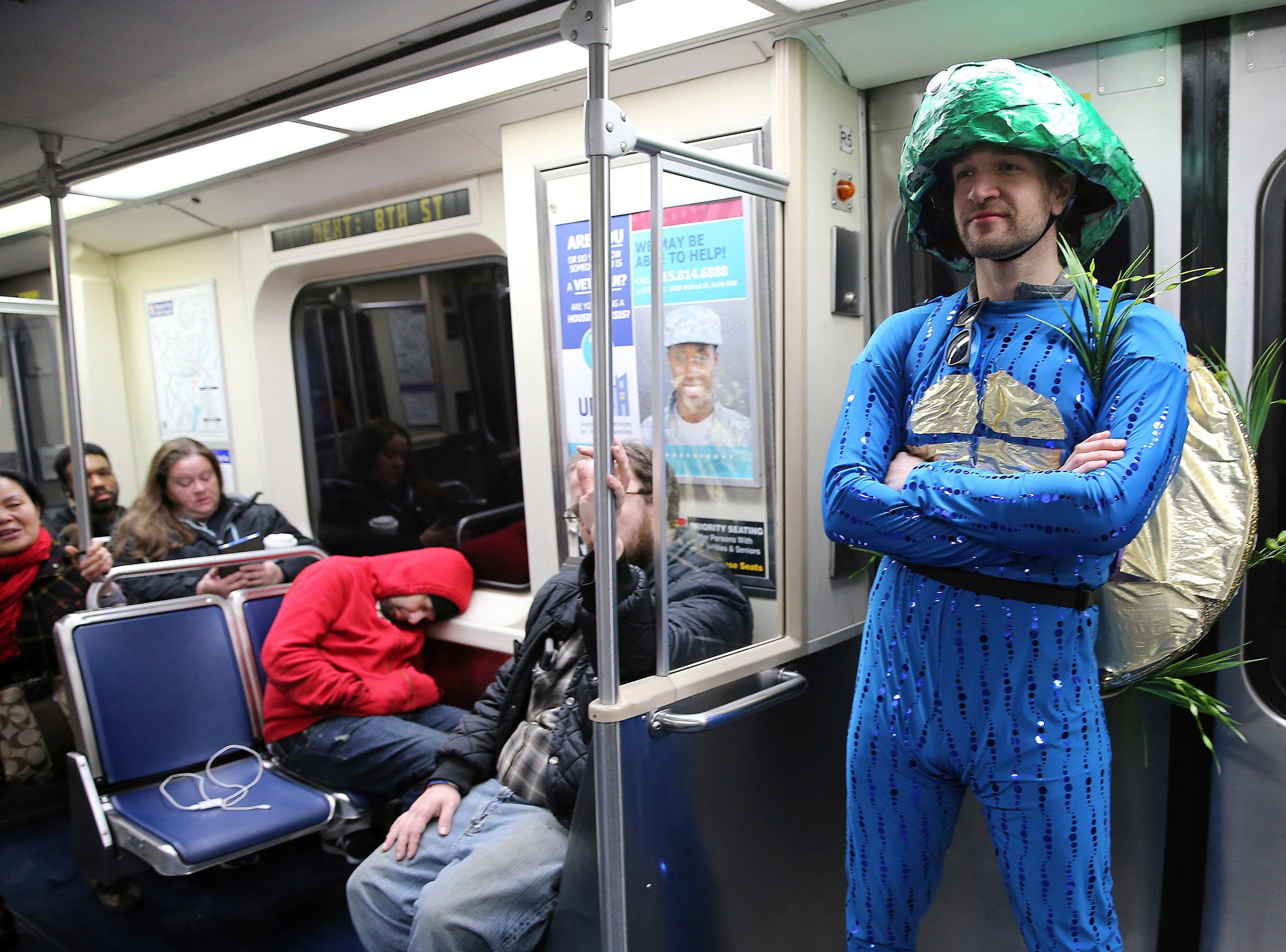 Drew Krause, a member of the Vaudevillians, rides the El to get his makeup for the Mummers Parade, Tuesday, Jan. 1, 2019, in Philadelphia. (David Maialetti/The Philadelphia Inquirer via AP)