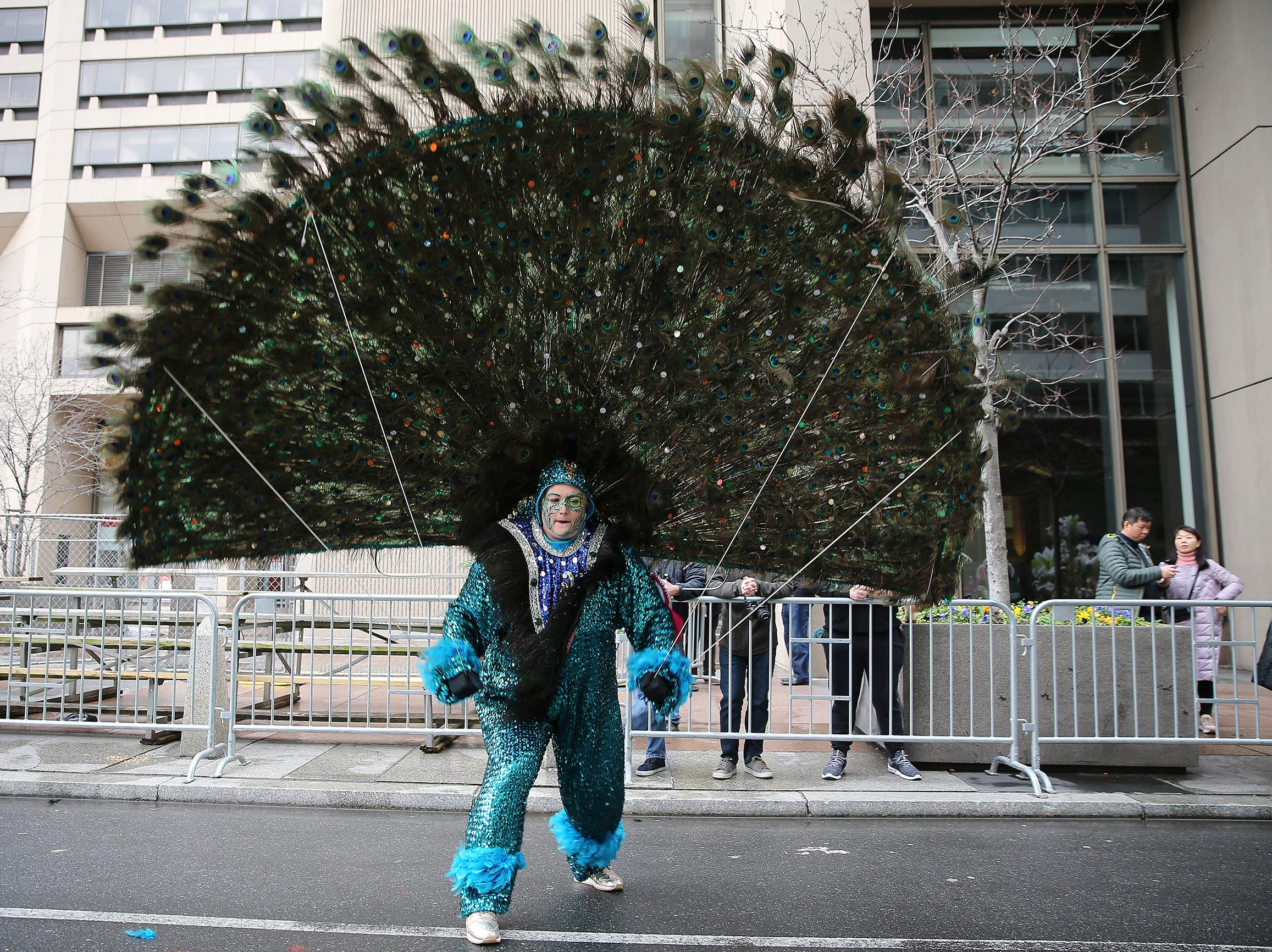 Jennifer Hensell, of Golden Sunrise Fancy Brigade, fights the wind as she waits for the start of the Mummers Parade, Tuesday, Jan. 1, 2019, in Philadelphia. (David Maialetti/The Philadelphia Inquirer via AP)