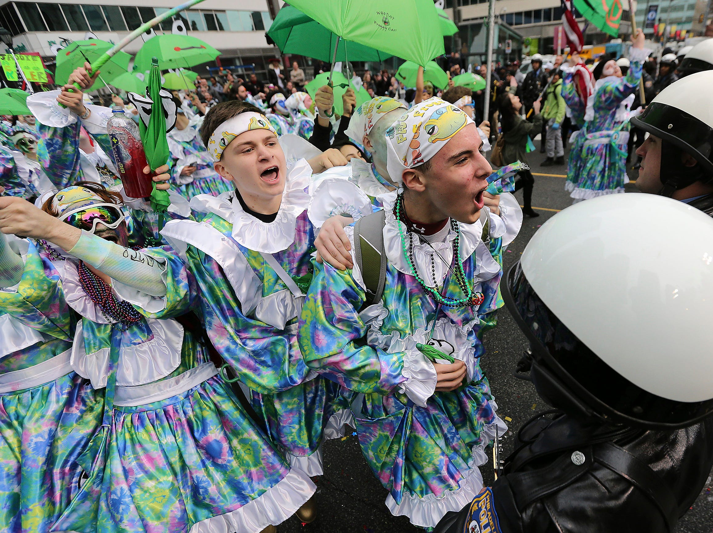 Members of Froggy Carr Wench Brigade strut in front of a row of police at City Hall during the Mummers Parade, Tuesday, Jan. 1, 2019, in Philadelphia. (David Maialetti/The Philadelphia Inquirer via AP)