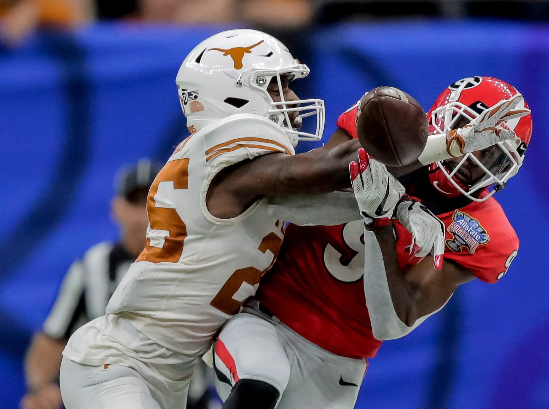 Texas Longhorns defensive back B.J. Foster (25) breaks up a pass to Georgia Bulldogs wide receiver Jeremiah Holloman (9) during the third quarter in the Sugar Bowl.