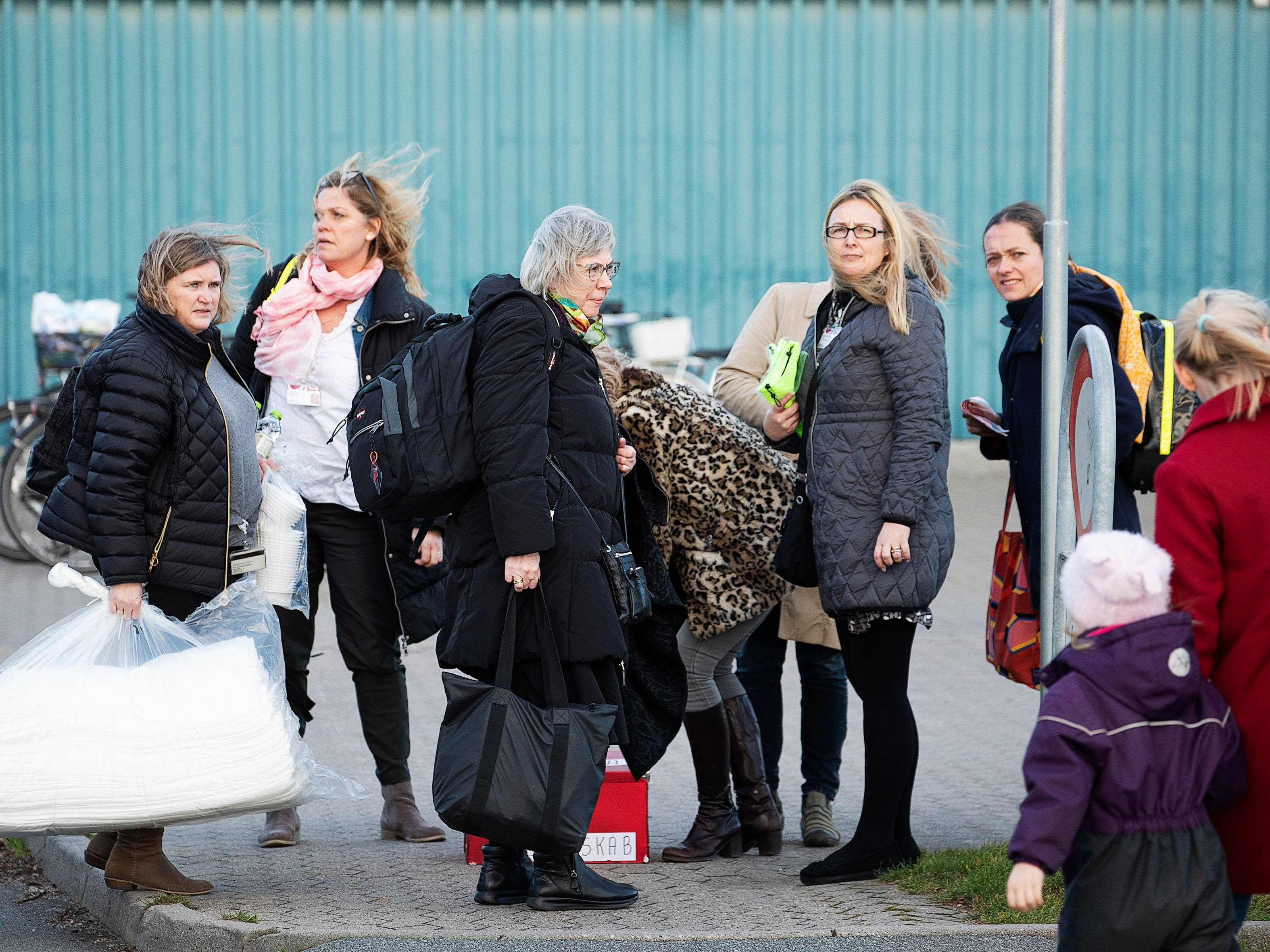 "Uninjured passengers who were on board a train involved in an accident on the Great Belt arrive at Nyborg Sports Center where a temporary crisis center has been set up, in Nyborg, Denmark, Wednesday, Jan. 2, 2019.  A passenger train on a bridge linking central Denmark's islands hit an ""unknown object"" early Wednesday, killing at least six people and injuring over a dozen others, Danish police said. Danish media reported that a tarpaulin on a freight train hit the passenger train, which was going in the opposite direction, prompting it to brake violently. Police spokesman Arne Gram said the passenger train ""hit an unknown object,"" but did not further comment. (Carsten Bundgaard Andersen/Ritzau Scanpix via AP) ORG XMIT: AMB806"