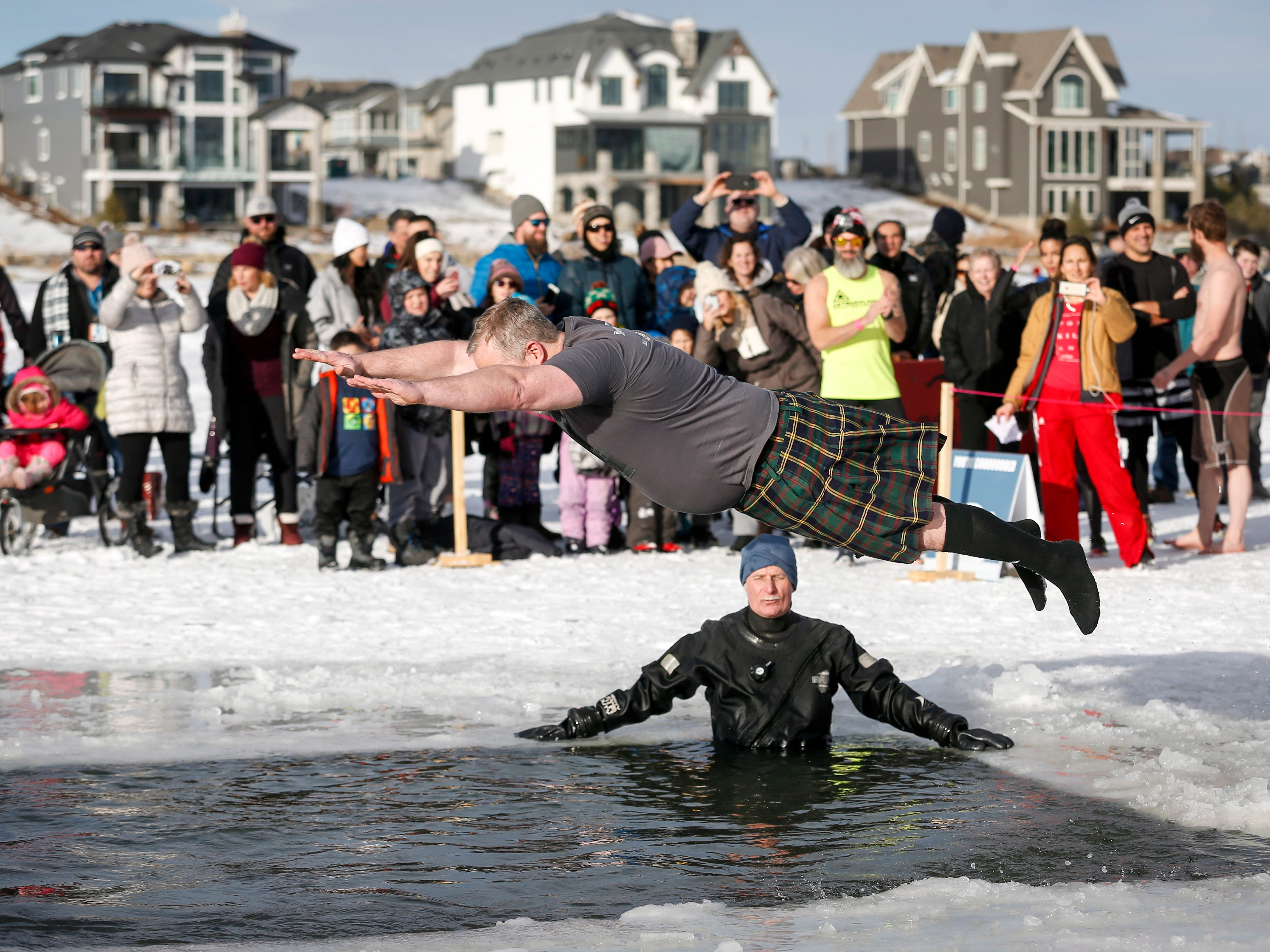 A participant leaps into the water in the 10th annual Polar Plunge in Calgary, Canada.