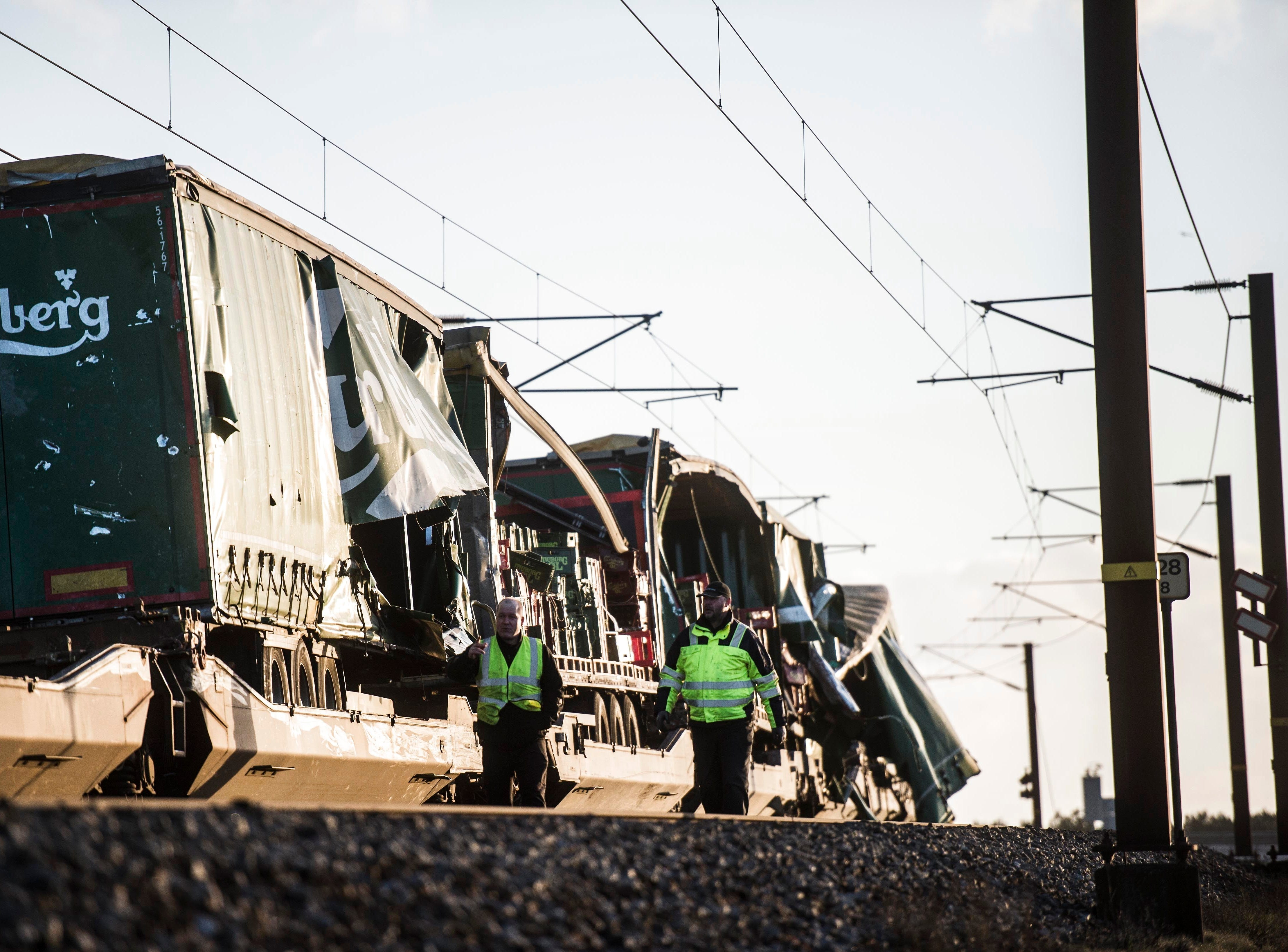 People walk near damaged cargo compartments on a train parked near the Storebaelt bridge, near Nyborg in Denmark, Wednesday, Jan. 2, 2019. Danish police say several people have been killed in a train accident on a bridge linking the central islands of Zealand and Funen. Police did not provide further details about those killed or the number of people injured in Wednesday's incident, which took place about 8 a.m. local time. Danish media reported that a tarpaulin on a freight train hit a passenger train going in the opposite direction, prompting it to brake suddenly. (Tim K. Jensen/Ritzau Scanpix via AP) ORG XMIT: TH804