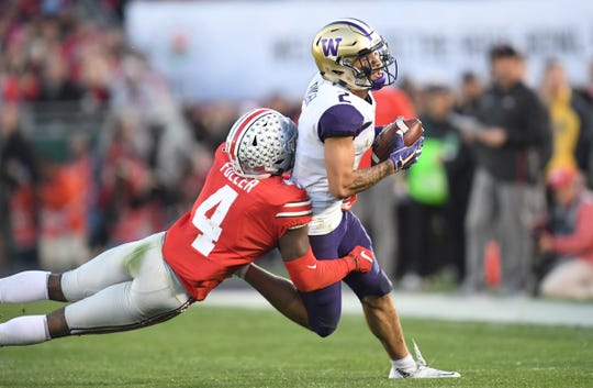 Washington Huskies wide receiver Aaron Fuller (2) runs against Ohio State Buckeyes safety Jordan Fuller (4) in the fourth quarter in the Rose Bowl.