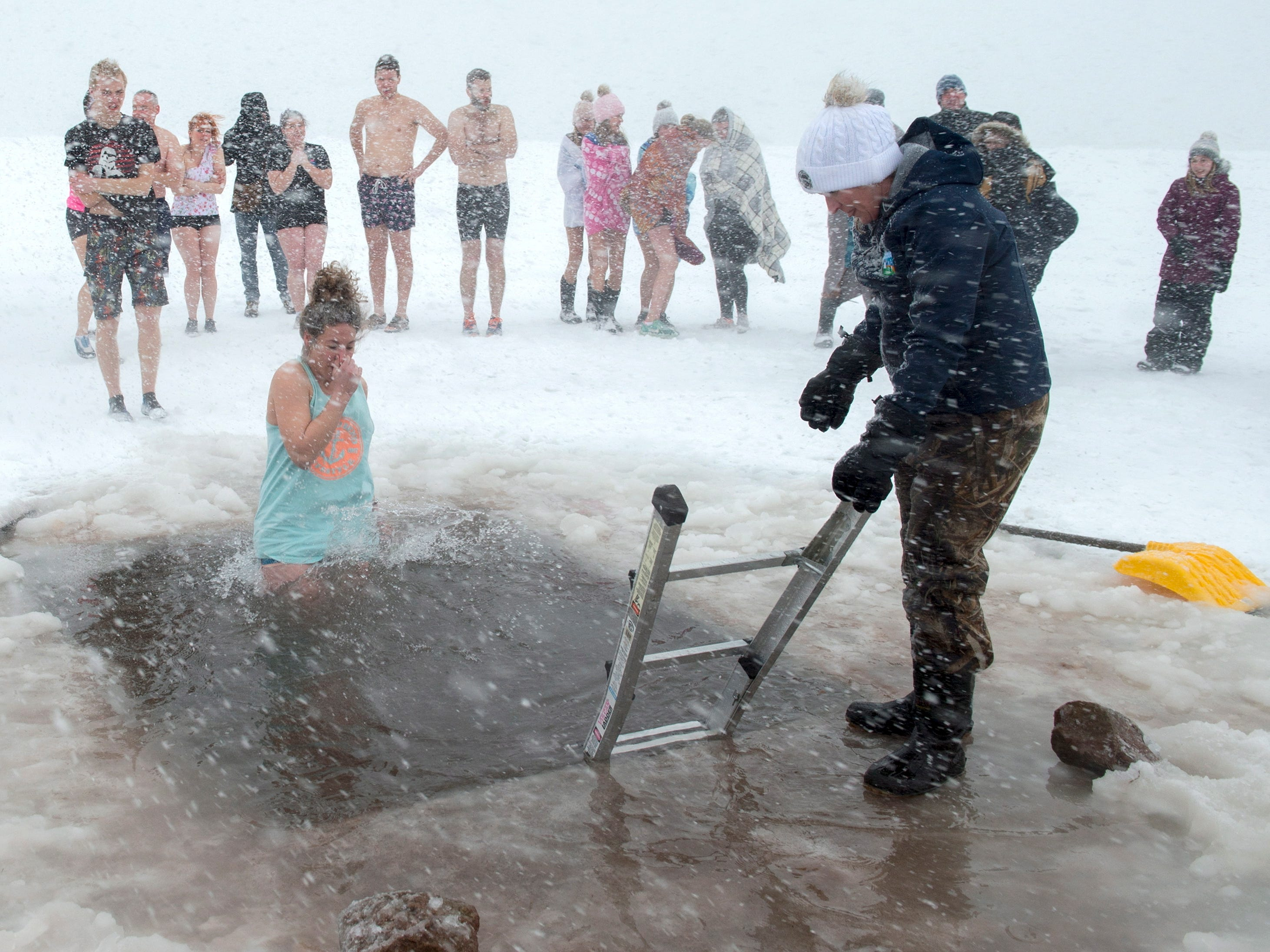 Swimmers brave stormy conditions as they participate in the annual New Year's Polar Bear Club dip in Charlottetown harbor on Prince Edward Island, Canada.