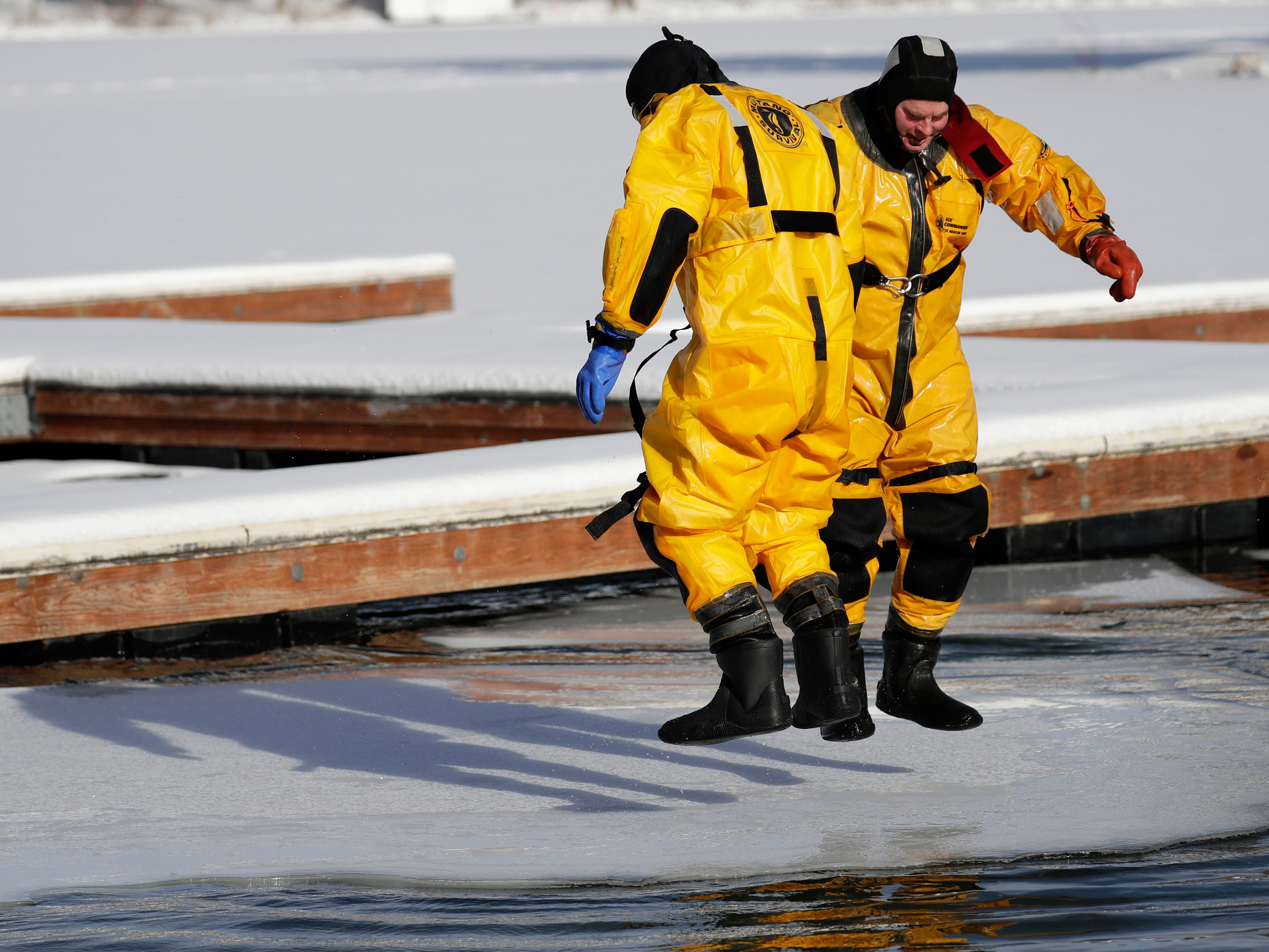 Waupaca firefighter Scott Obremski, left, and Lt. Pete Jungers jump up and down trying to break off the edge of the ice during the Polar Bear Plunge at Becker Marine on Lime Kiln Lake in Waupaca, Wis.