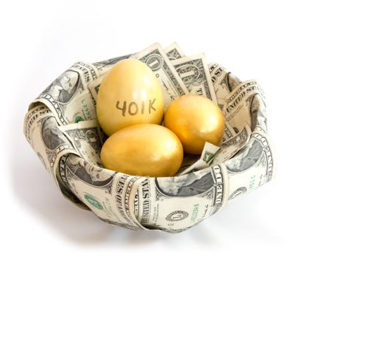 Image of golden eggs in a nest made from dollar bills.  One of the gold eggs is labeled 401k, indicating a retirement savings account.  The nest is set on a white background.  The nest eggs are nested in a nest constructed from money.