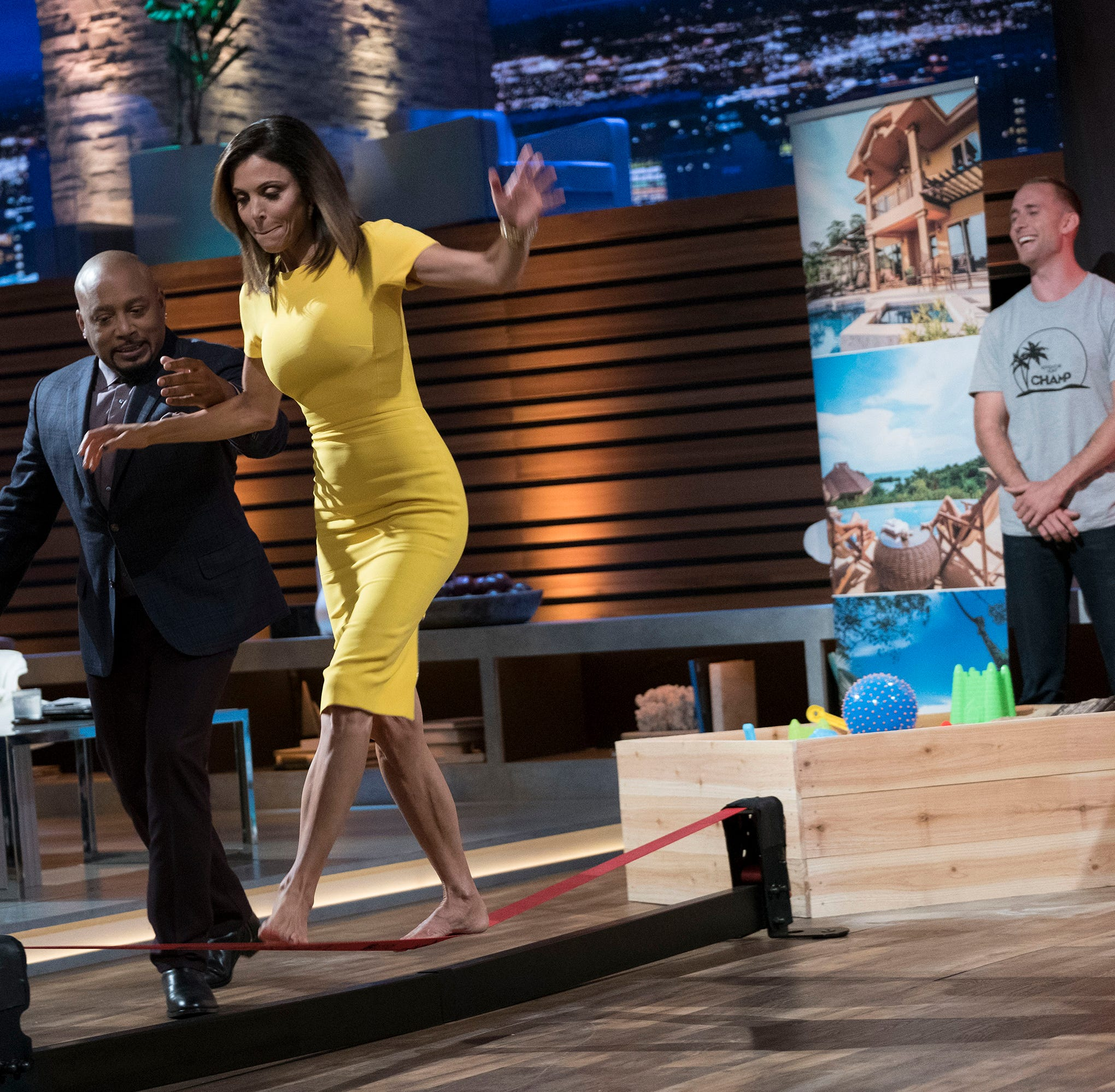 "Guest ""shark"" Bethenny Frankel, assisted by Daymond John, tries out an obstacle on an Adventure Hunt game on ABC's ""Shark Tank."""