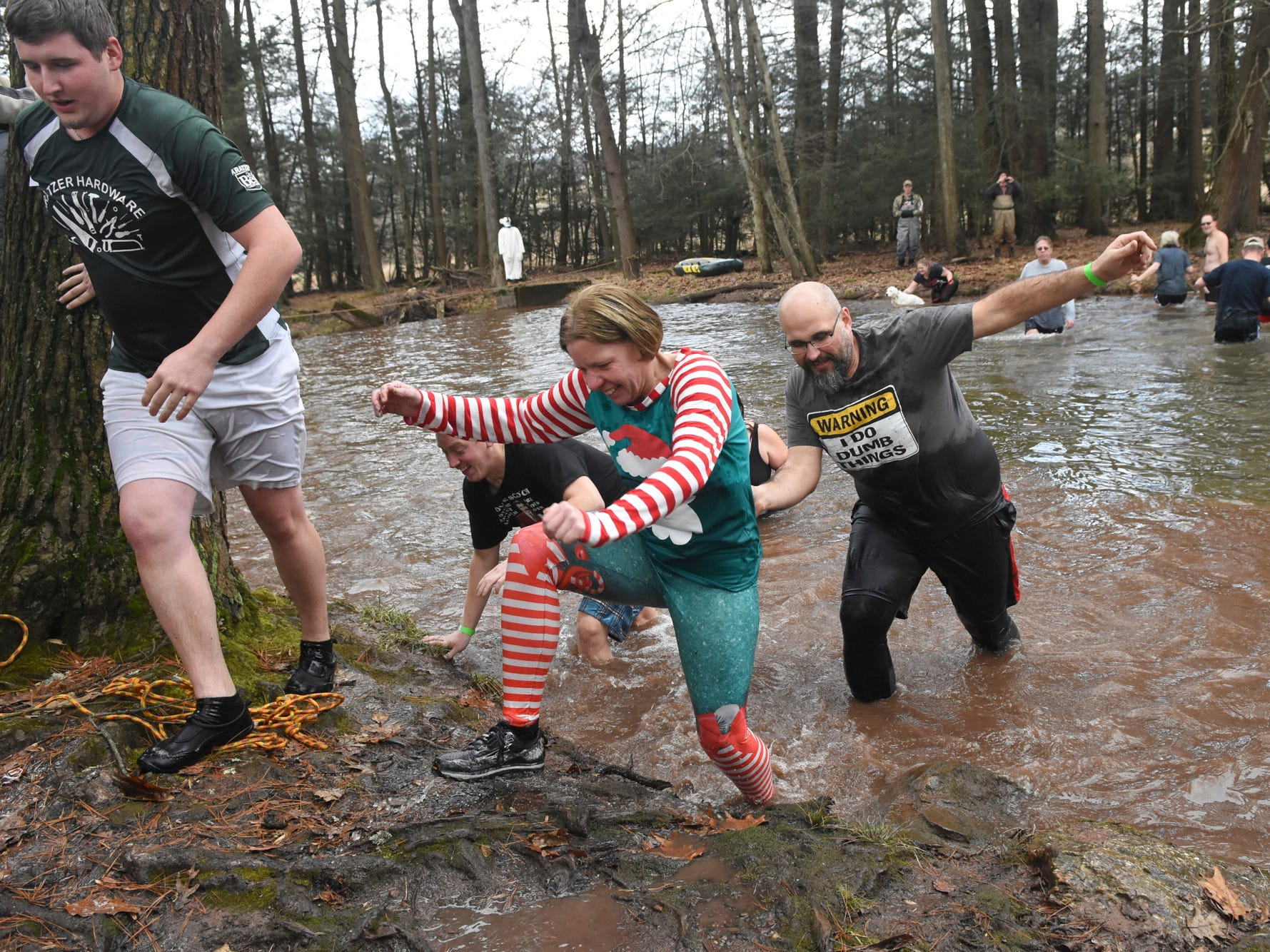 Lisa Lasco, center, and Jason Smith make their way out of Pine Creek during the 10th annual Pine Creek Polar Bear Plunge in Valley View Park in Valley View, Pa. The event benefits Pine Creek Trout Nursery.