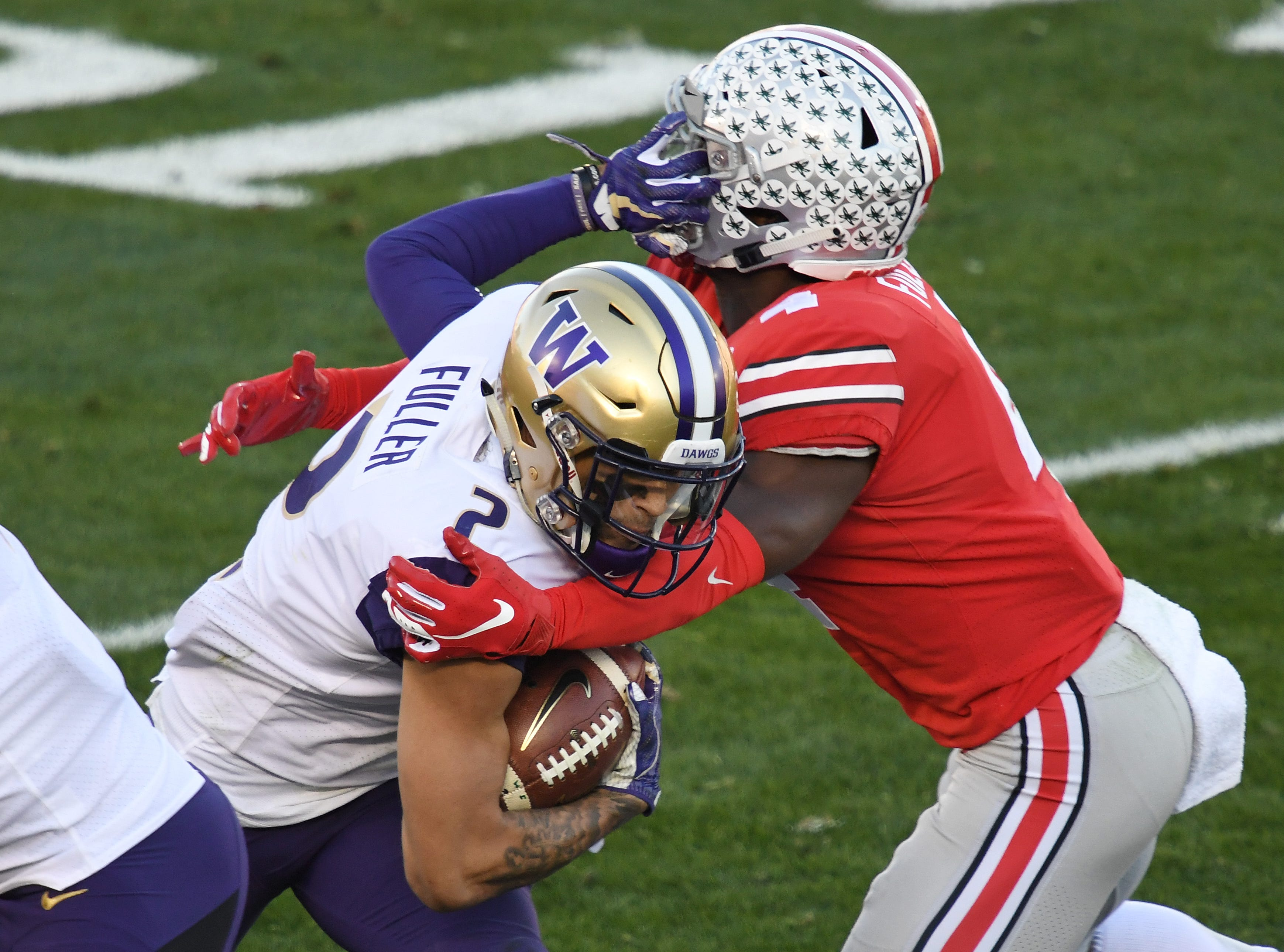 Washington Huskies wide receiver Aaron Fuller (2) runs against Ohio State Buckeyes safety Jordan Fuller (4) in the first half of the Rose Bowl.