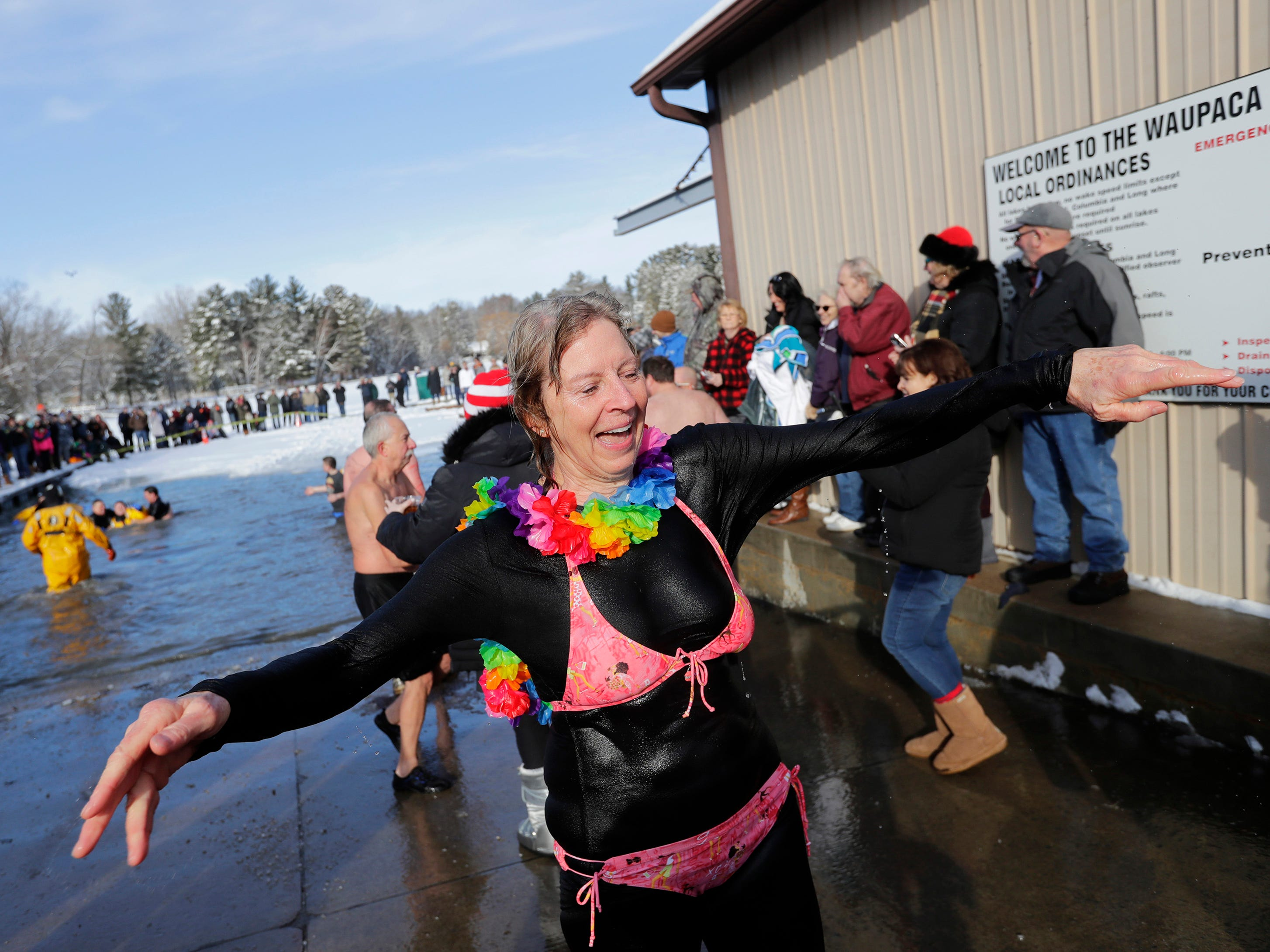 Sara Bredesen emerges from the cold water during the Polar Bear Plunge at Becker Marine on Lime Kiln Lake in Waupaca, Wis.