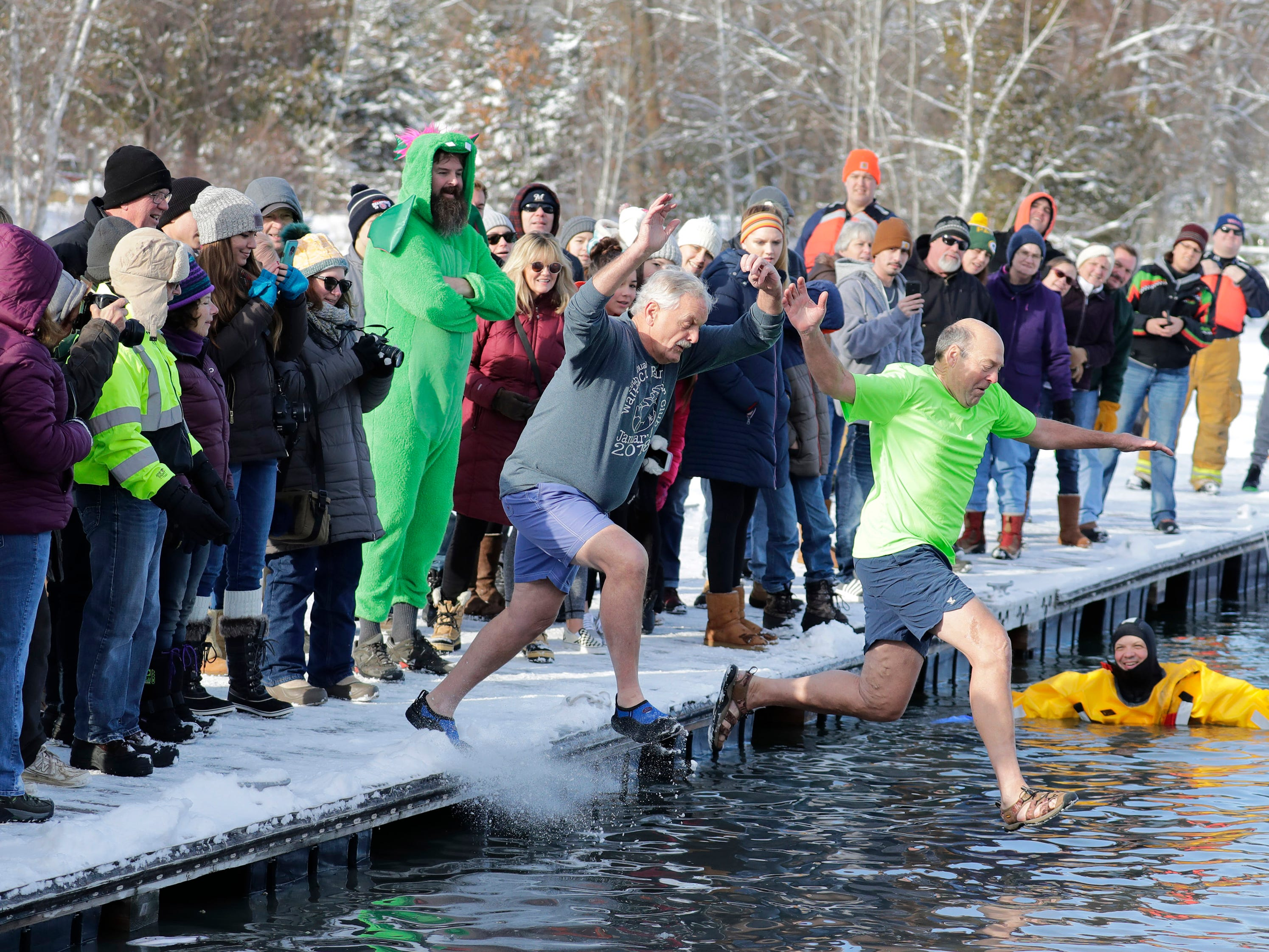 Joe Farmer, left, and Larry Gordon jump into frigid waters during the Polar Bear Plunge at Becker Marine on Lime Kiln Lake in Waupaca, Wis.