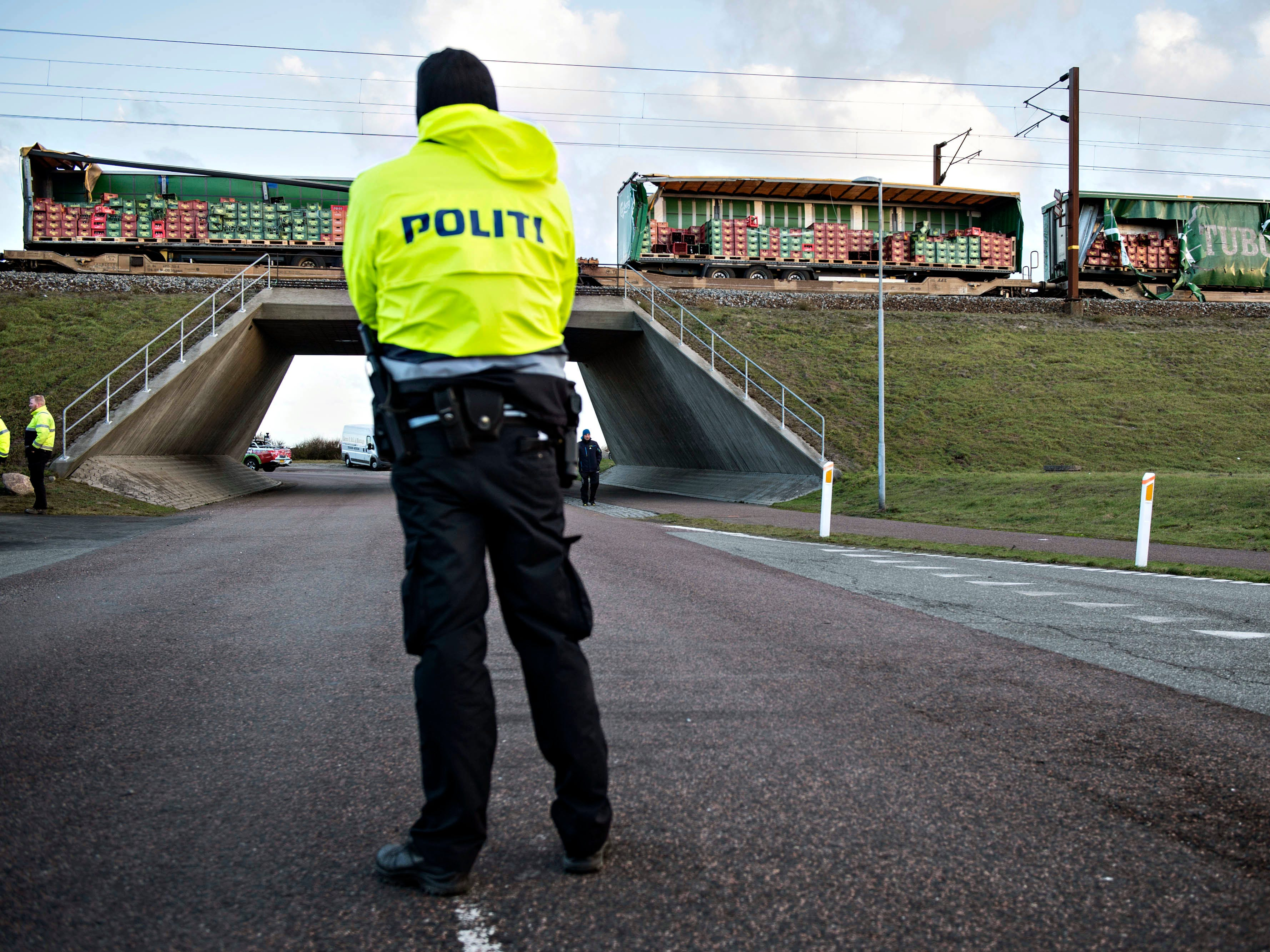"A police stands guard near the scene of a train accident, on the Great Belt Bridge, in Nyborg, Denmark,  Wednesday, Jan. 2,  2019.  At least six people were killed in a train accident early Wednesday on a Danish bridge linking the central islands of Zealand and Funen, according to the rail operator. Authorities said several others were injured. Police spokesman Arne Gram said the passenger train ""hit an unknown object,"" but did not further comment. (Michael Bager/Ritzau Scanpix via AP) ORG XMIT: AMB803"