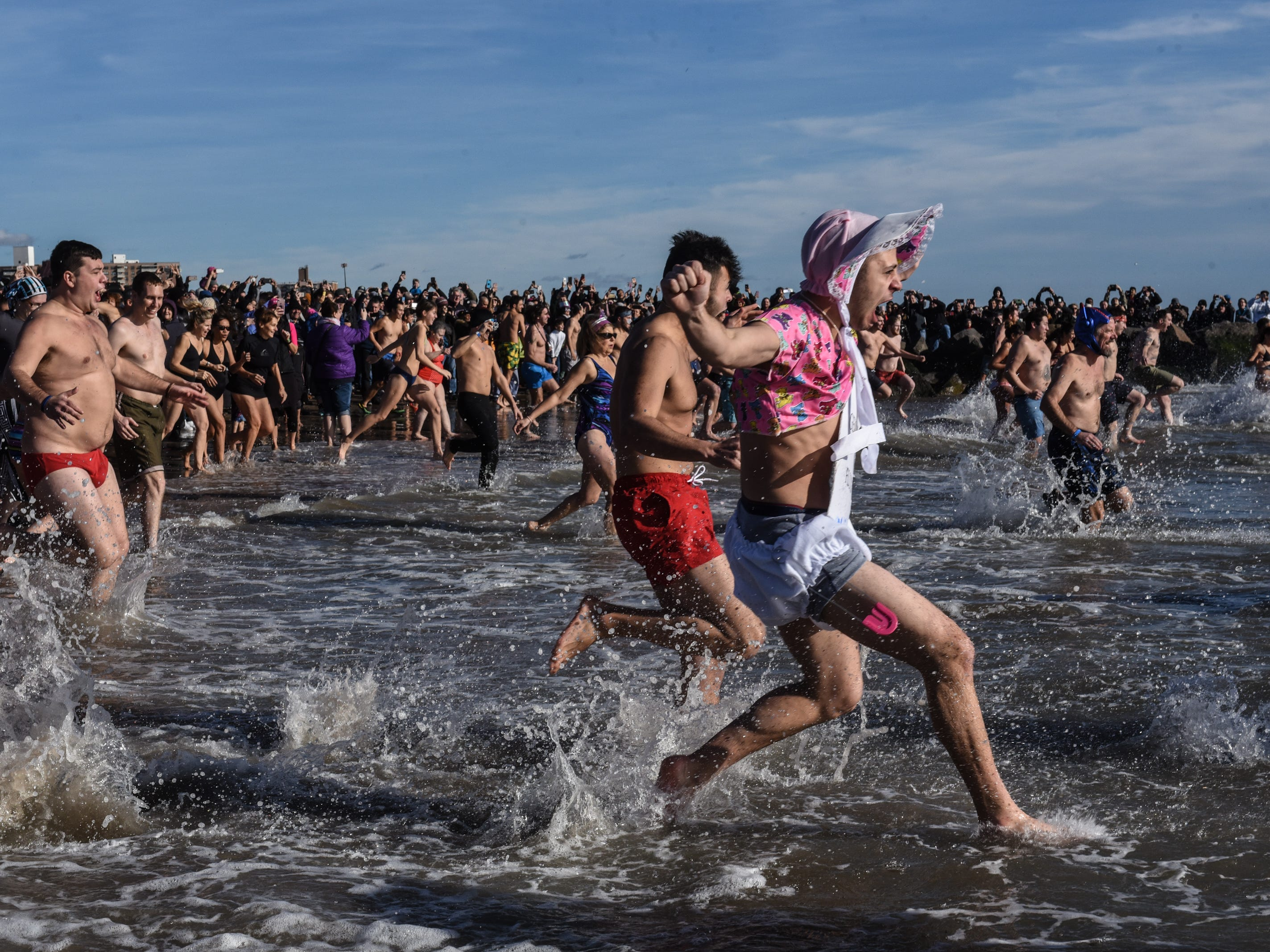 People jump into the Atlantic Ocean during the annual Polar Bear Plunge on New Year's Day in Coney Island on in the Brooklyn borough of New York City.