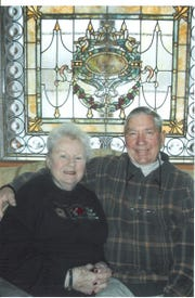 Sandy Scanlon and her husband, William J. Scanlon around 2008, seated in front of a stained glass window once at the top of a stairwell in the old Johnson Mansion.