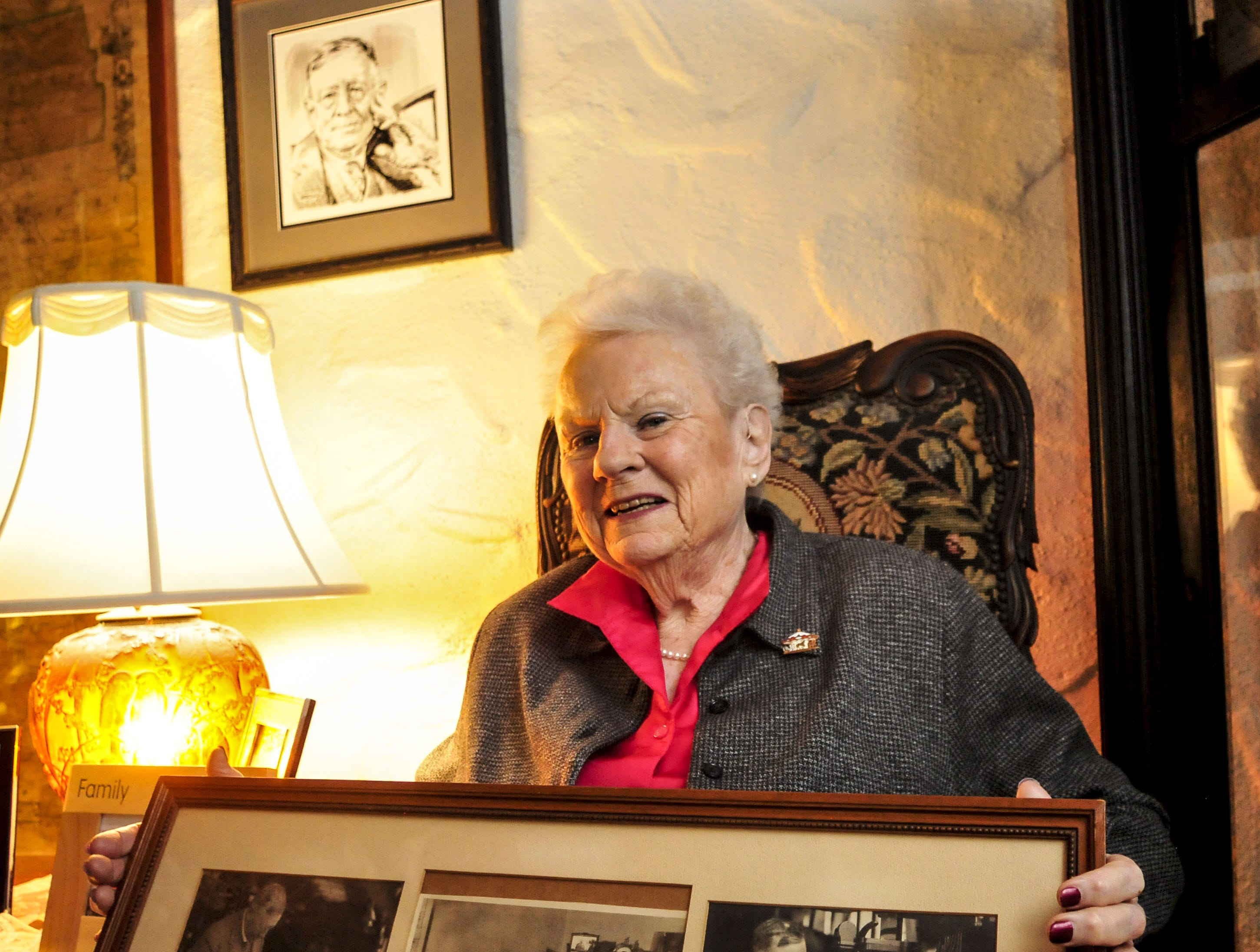 Sandra Scanlon, granddaughter of  Broome County industrialist George F. Johnson, sits in one of his antique chairs holding photos of him at her Windsor home. Scanlon was selected as grand marshal of Endicott's 2013 holiday parade.
