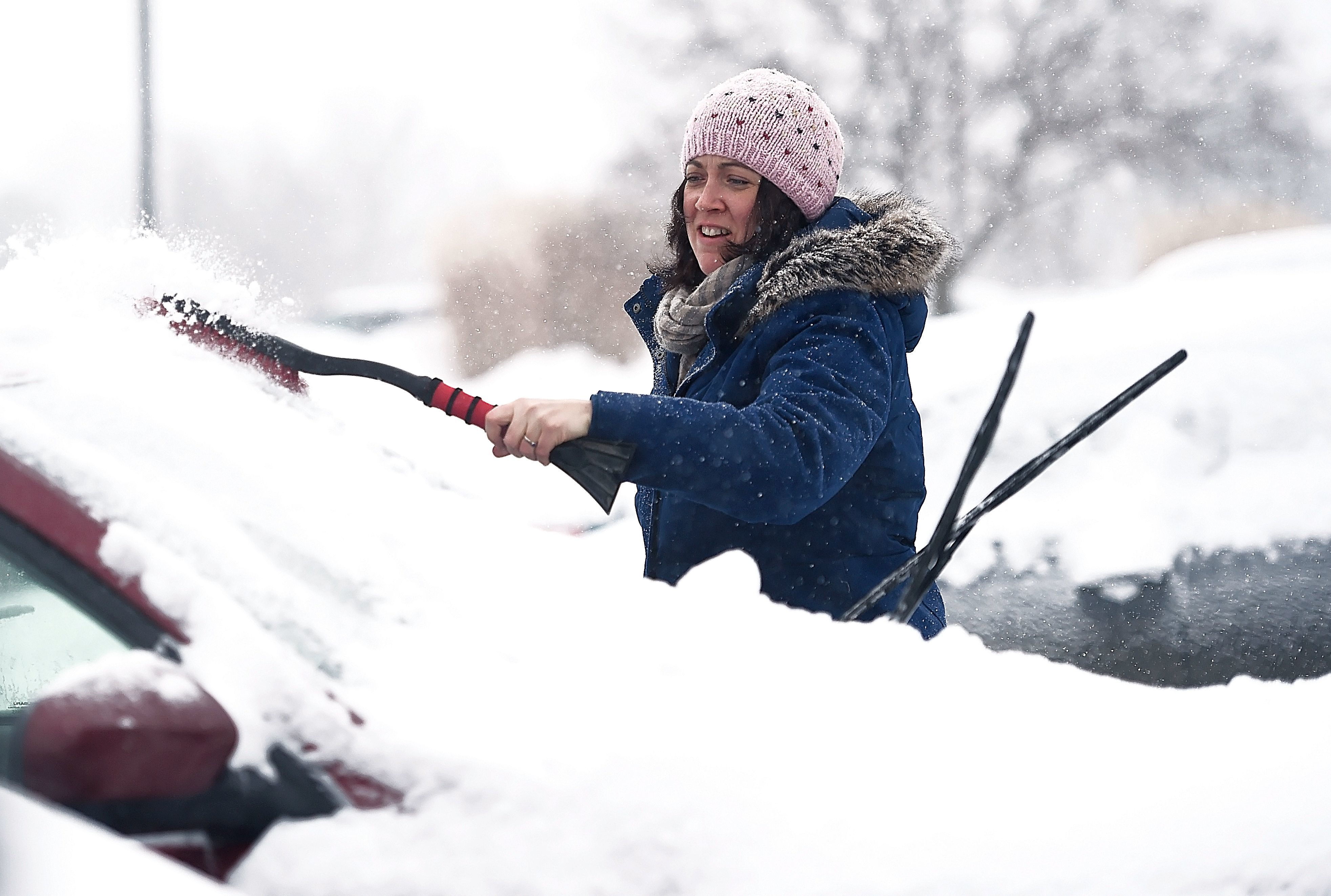 Jennifer Lyons, an art history professor at Ithaca College, cleans off her car in a parking lot at the school. Although many schools cancelled due to weather, Ithaca College and Cornell University remained open for classes. February 7, 2018.