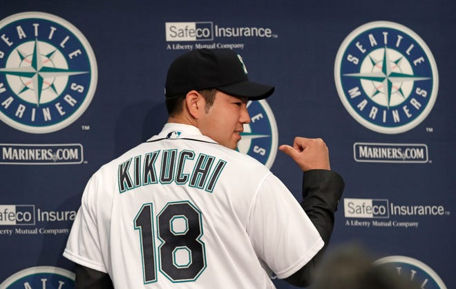 New Mariners pitcher Yusei Kikuchi tries on his new jersey after being introduced on Thursday in Seattle.