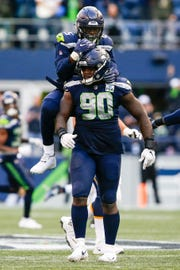Seahawks defensive tackle Jarran Reed (90) celebrates with  defensive end Frank Clark (55) following a sack against the Los Angeles Chargers during a November game at CenturyLink Field.