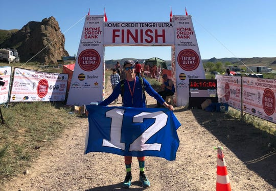 Greg Nance, a devoted Seattle Seahawks fan, displays his 12th man flag at the finish line of the Ultra Marathon of the Great Steppe in Kazakhstan.