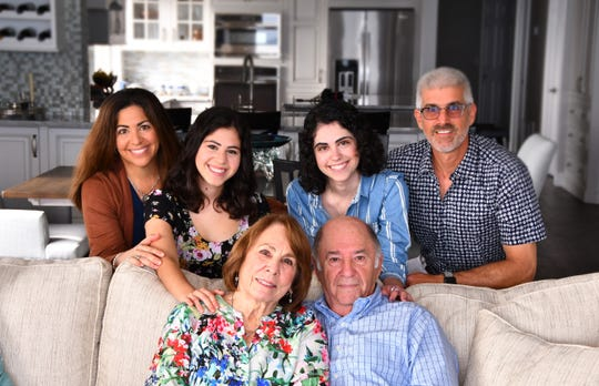 "Alex Dixon (in the blue shirt in the back row) with her family. (Back row left to right) Juli (mom)  Jessica (sister) Marc (dad),  front row grandparents Joy and Harvey Inventasch. Alex Dixon had a near fatal stroke when she was 12 and had to relearn almost everything. She is now a junior at UCF. Her Mom, Dr. Juli Dixon and her sister Jessica wrote a book, ""A Stroke of Luck"" on her journey back."