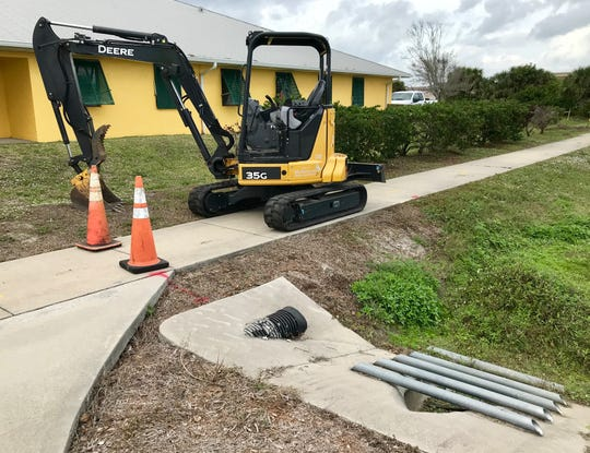 A city of Melbourne compact excavator is parked at the suspected water main leak site at South Patrick Shores and Jackson Avenue in Satellite Beach.