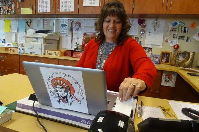 Justine Moodespaugh, secretary at Bucyrus High School, pulls an identification label for a school visitor from the building's new visitor management system.