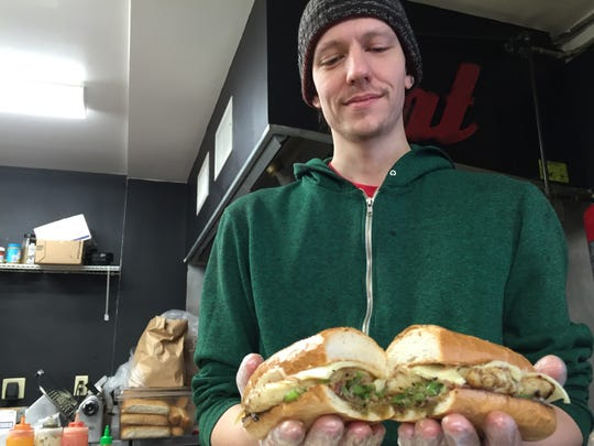 Chad Bigelow, head chef and general manager at the Henry Street Deli, shows the Burlington eatery's chipotle grilled-chicken sandwich.