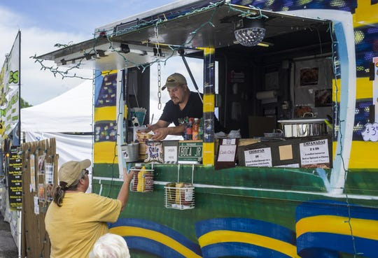 Javier Zirko of Grand Isle serves a customer some Argentinean cuisine from the Dale Boca food truck at the Champlain Valley Fair in Essex on Tuesday, August 29, 2017.