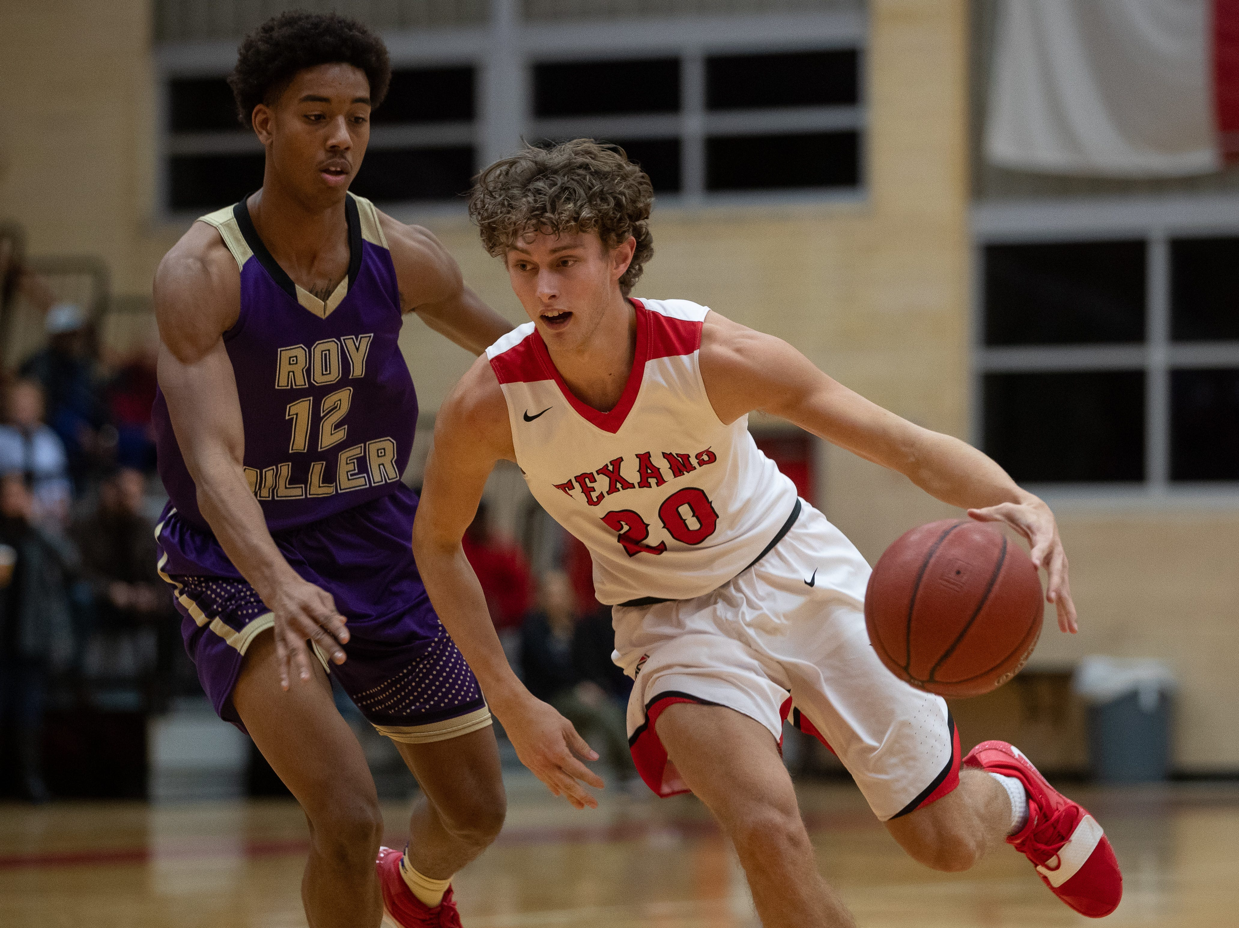 Ray's Trevor Allison drives the ball past Miller's Xavier Calladner during the first quarter of their game at Ray High School on Wednesday, Jan. 2, 2018.