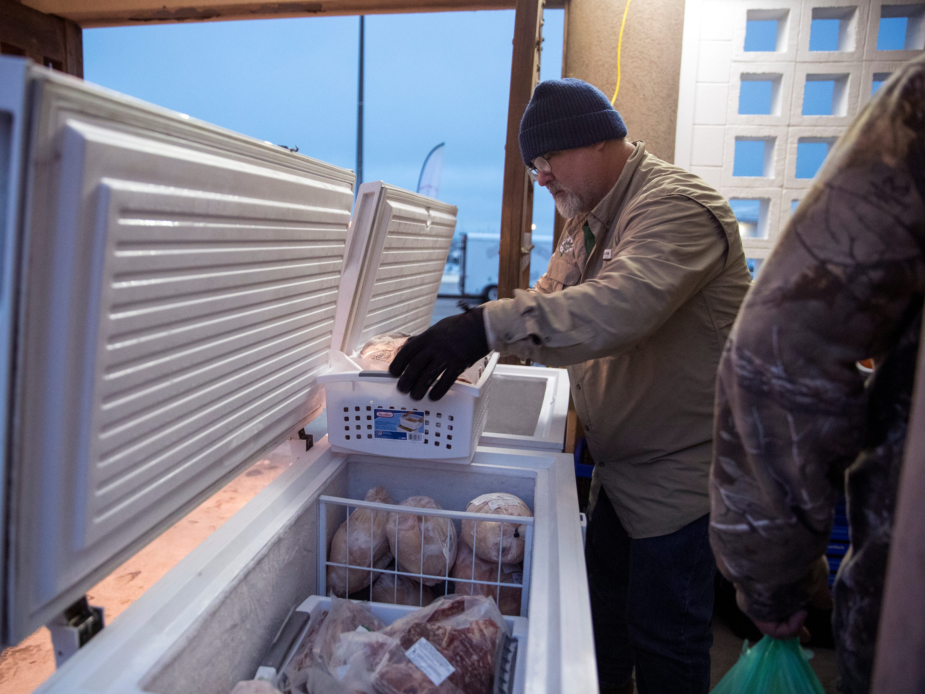 Wes Burns (left), owner of Future Focus Farms, pulls meat out of a freezer for a customer at the Corpus Christi Downtown Farmers Market at the first market of the year on January 2, 2019. Farmers markets help create community and producers get to know the consumers that shop with them, said Aislynn Campbell, founder of the market. It also enables the farmer, or business owner to meet new customers and grow their business.