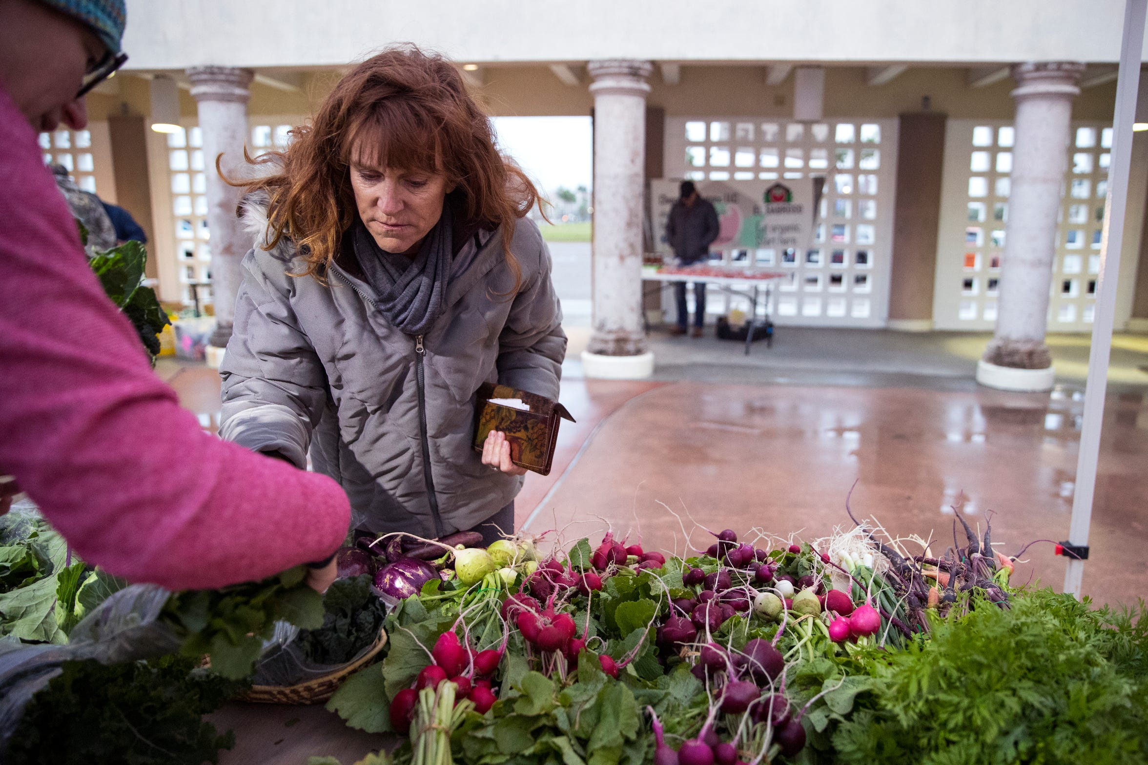 Michelle Kish (left) helps Mariah McQueen as she shops for vegetables at the Corpus Christi Downtown Farmers Market at their first market of the year on January 2, 2019. Farmers markets help create community and producers get to know the consumers that shop with them, said Aislynn Campbell, founder of the market. It also enables the farmer, or business owner to meet new customers and grow their business.