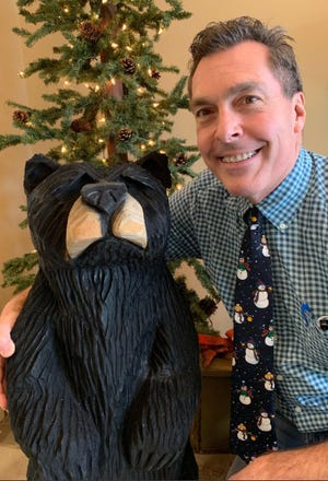 Dr. Tom Kadar poses with a hand-carved wooden bear that was returned after a theft at his Sewell office.