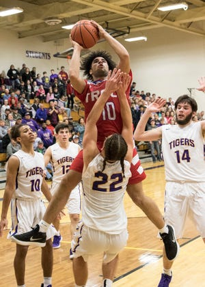 Zane Trace junior Cam Evans jumps over a McClain player to score for Zane Trace Wednesday night at McClain High School. McClain defeated Zane Trace 61-60.