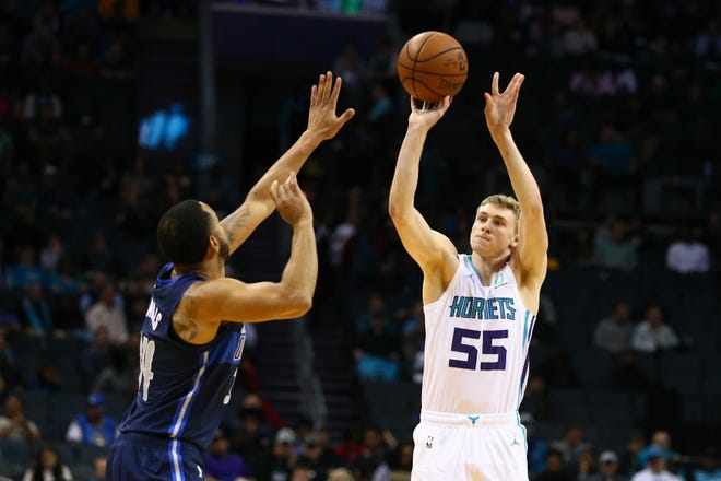 Charlotte Hornets guard J.P. Macura (55) shoots a 3-point basket against Dallas Mavericks guard Devin Harris (34) in the second half at Spectrum Center on Jan. 2.