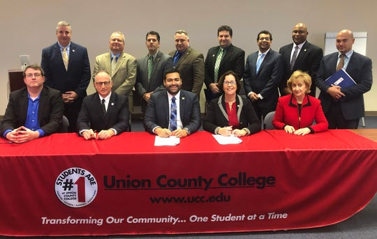 Seated at the table for the signing are County Manager Oatman, Acting Prosecutor Monahan, Freeholder Chairman Granados, Dr. McMenamin, and Dr. Lown.
