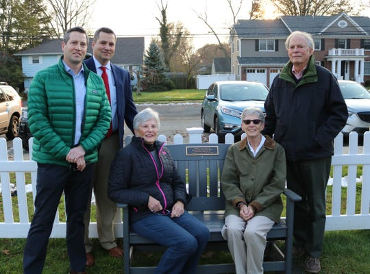 Members of the Juelis family, including sons Mark and Craig (left) and husband John, attend a dedication ceremony for a memorial bench in honor of veteran educator Mary Jo Juelis who passed away in 2017.