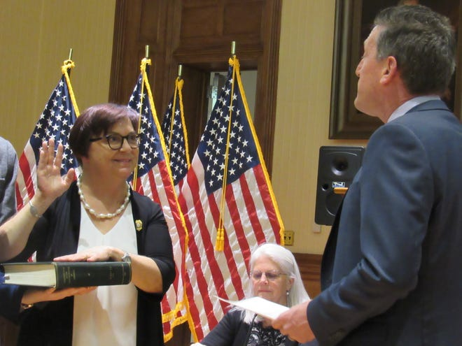 With a hand on a copy of the Constitution, Betsy Driver is sworn in as mayor of Flemington by Assemblyman Andrew Zwicker.