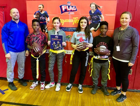 Students at McManus Middle School in Linden checking out new flag football equipment the school received through a grant from NFL Play 60. From left are physical education teacher Patrick Migliore; seventh-graders Ashton Armstead, Michelle Gasior, Gabriela Grzebyk and Ryan Armstead; and physical education teacher Emilia Milewski.
