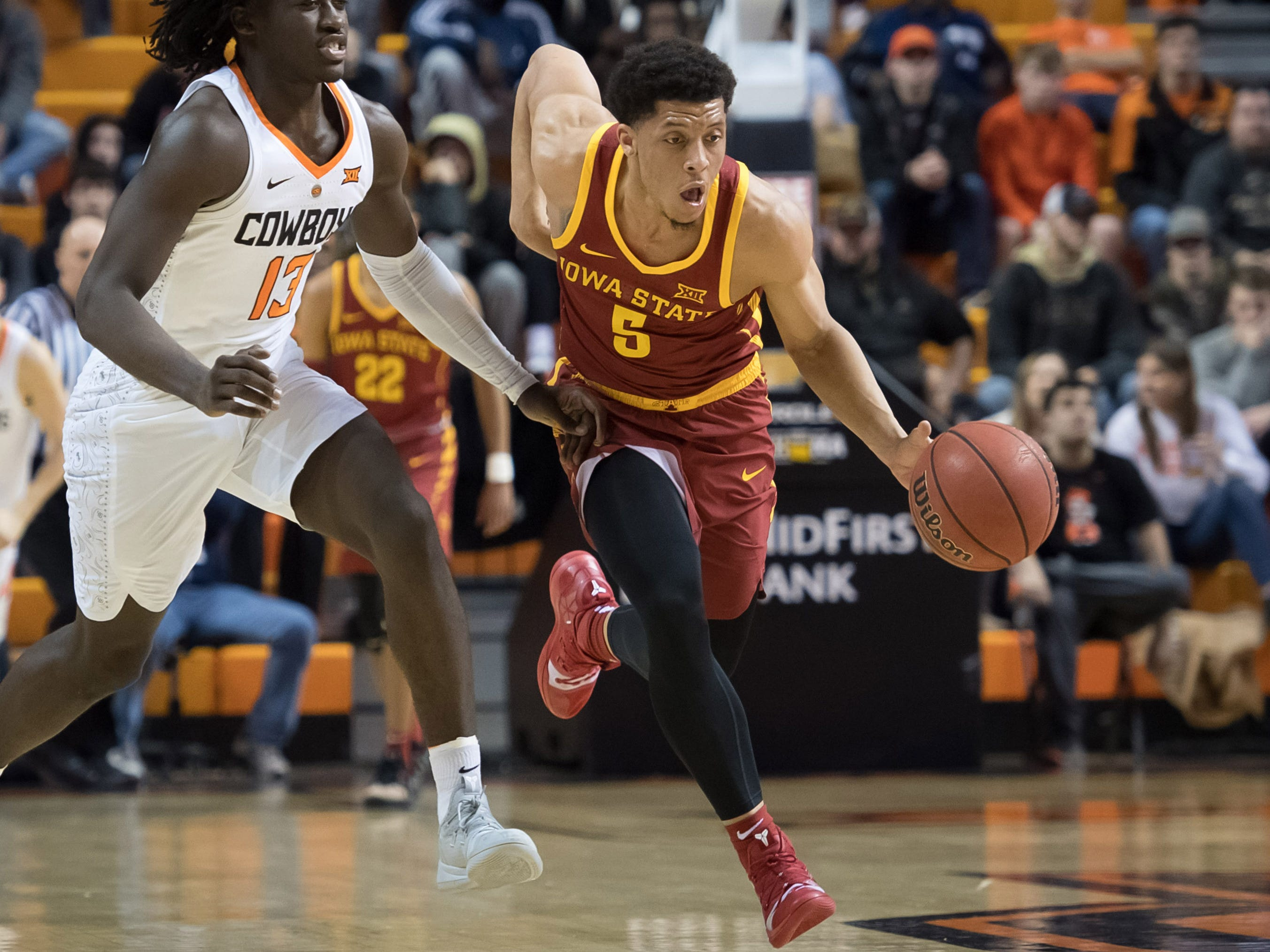 Jan 2, 2019; Stillwater, OK, USA; Iowa State Cyclones guard Lindell Wigginton (5) dribbles the ball past Oklahoma State Cowboys guard Isaac Likekele (13) during the first half at Gallagher-Iba Arena.