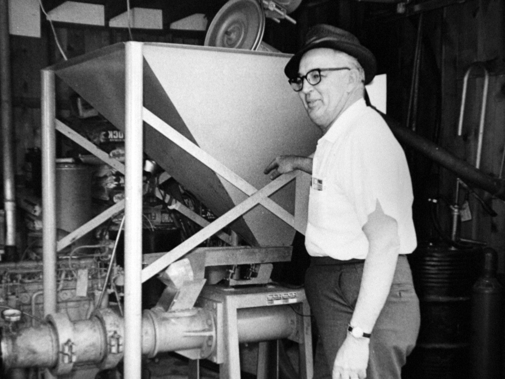 Wayne Fox, of Des Moines, is pictured in 1969 next to the soybean extruder he invented.
