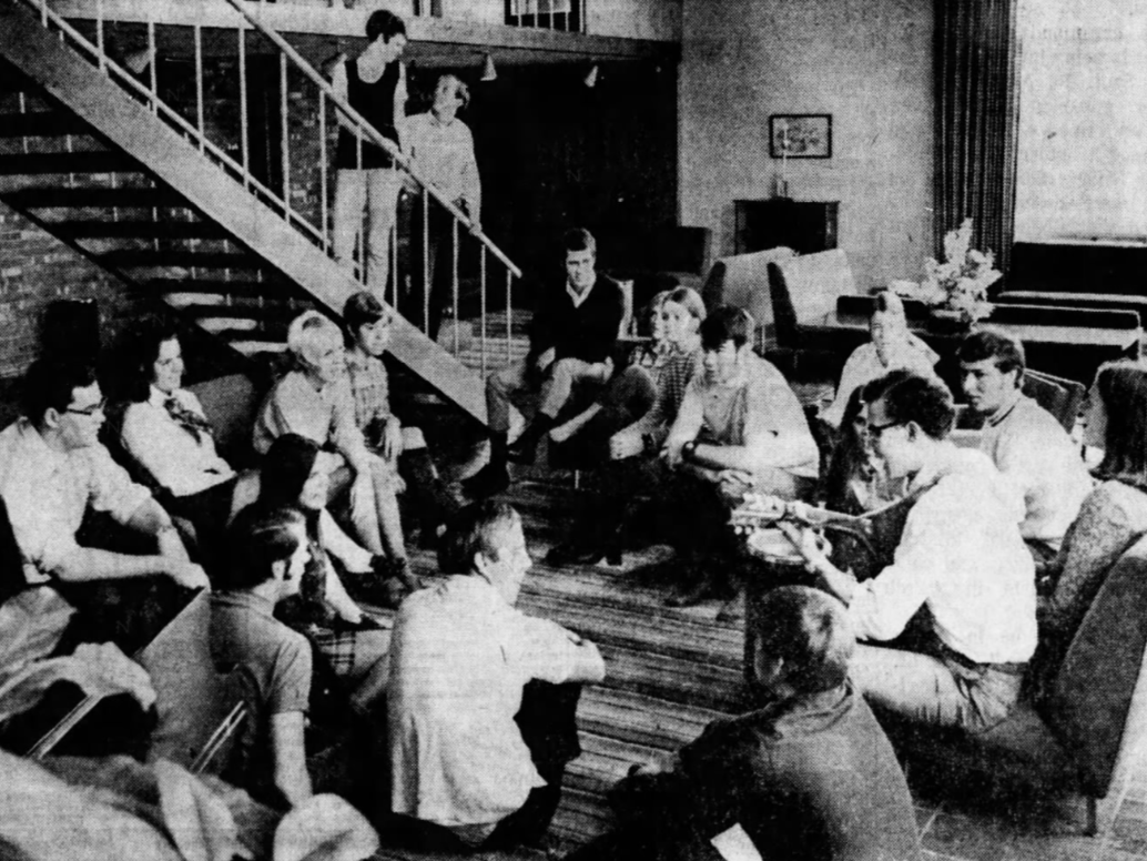 Drake University students fill the living room of Herriott Hall  to listen to Jack Holmquest, 20, a fine arts major from Webster City, play the guitar in September 1969.
