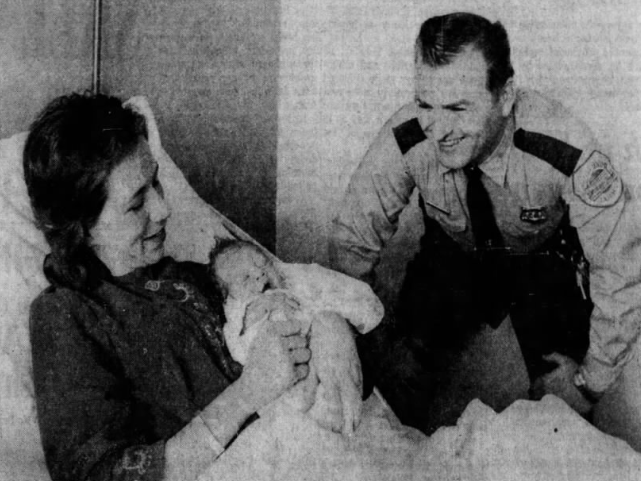 Des Moines Police officer Russell Nauman is all smiles as he visits with Mrs. Brian Armentrout, 27, and daughter Kimberley Marie at Mercy Hospital. Nauman assisted with the delivery of 6-pound, 10-ounce Kimberley, who was born in the East 39th Street home of her grandparents, Mr. and Mrs. Floyd Jewett.
