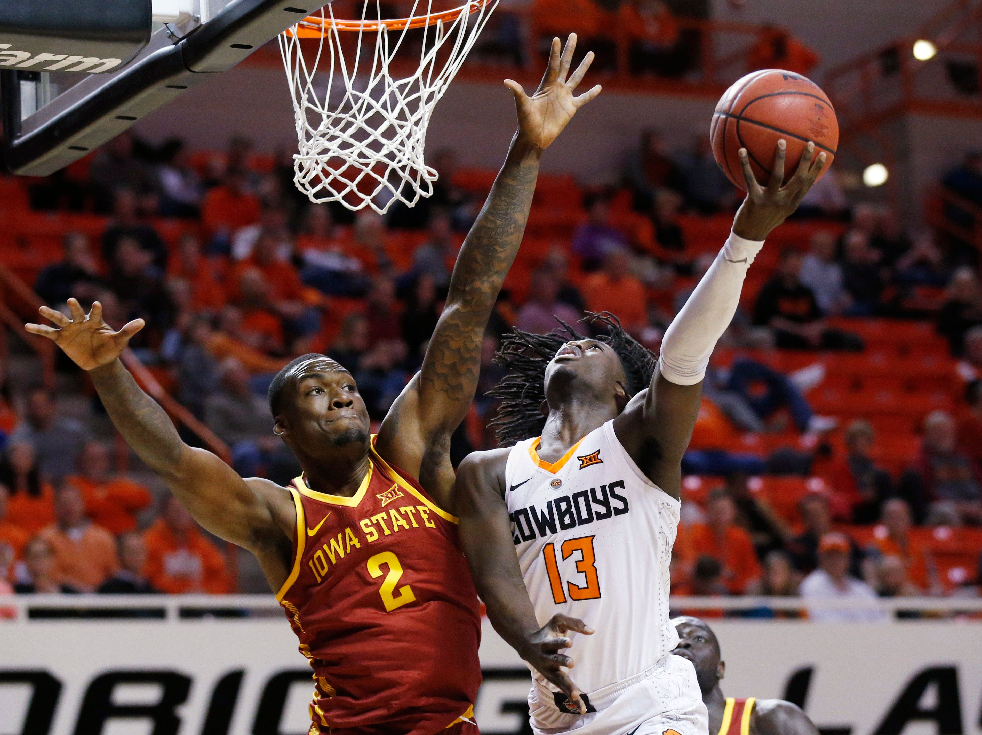 Oklahoma State guard Isaac Likekele (13) shoots as Iowa State forward Cameron Lard (2) defends during the first half of an NCAA college basketball game in Stillwater, Okla., Wednesday, Jan. 2, 2019. (AP Photo/Sue Ogrocki)