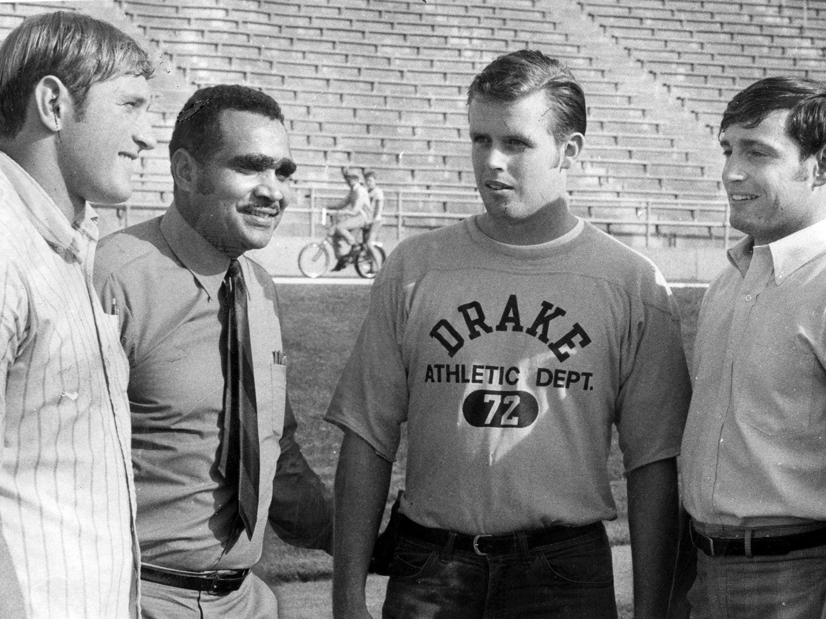 Drake University football legend Johnny Bright talks with the Bulldogs' three 1969 captains on the turf of Drake Stadium, where Bright gained fame (and record yardage) in 1949-1951. From left: defensive end John Knight, Bright, quarterback Gary McCoy and split end Duane Miller. Bright was named the greatest player in Drake's football history.