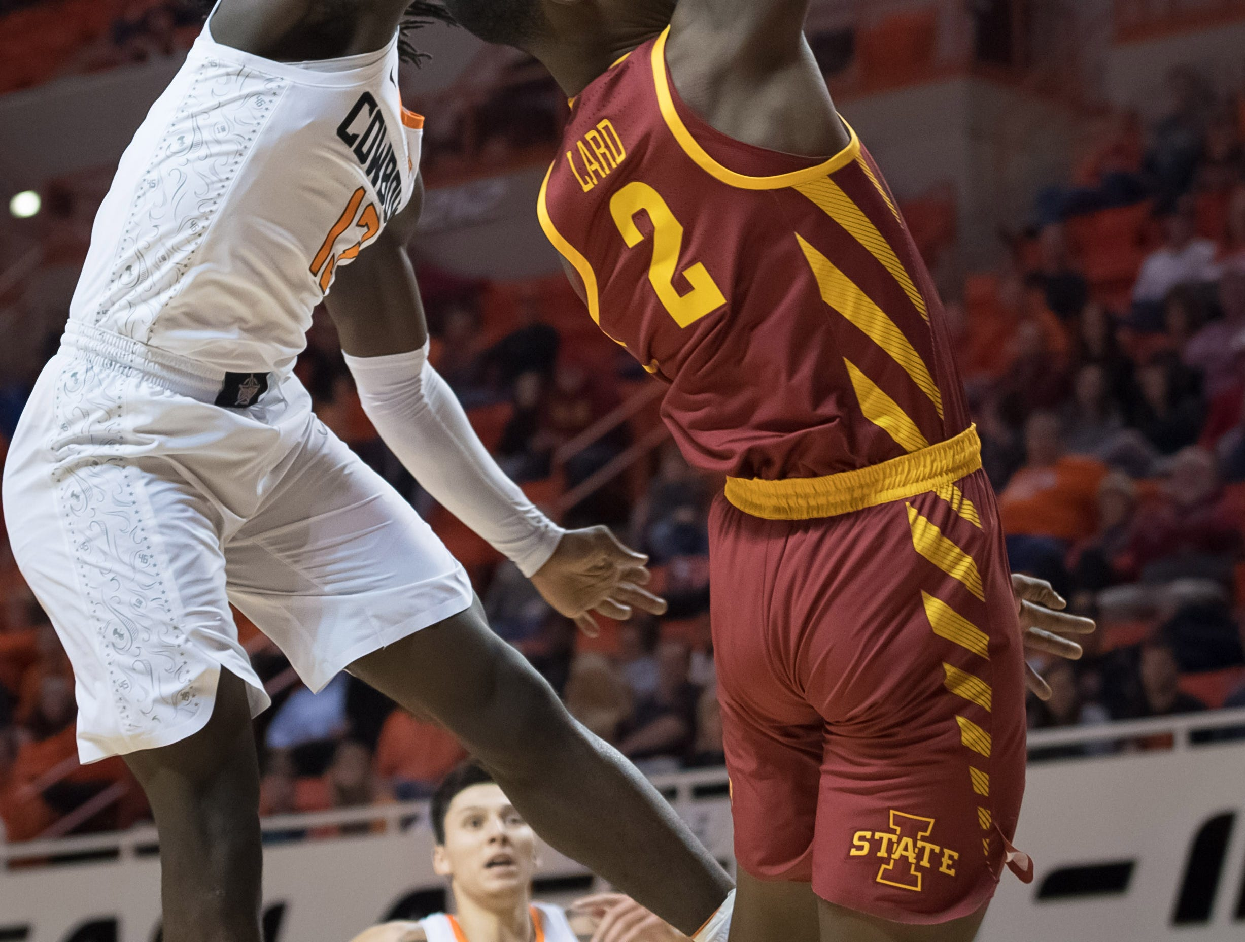Jan 2, 2019; Stillwater, OK, USA; Oklahoma State Cowboys guard Isaac Likekele (13) blocks a shot by Iowa State Cyclones forward Cameron Lard (2) during the first half at Gallagher-Iba Arena.