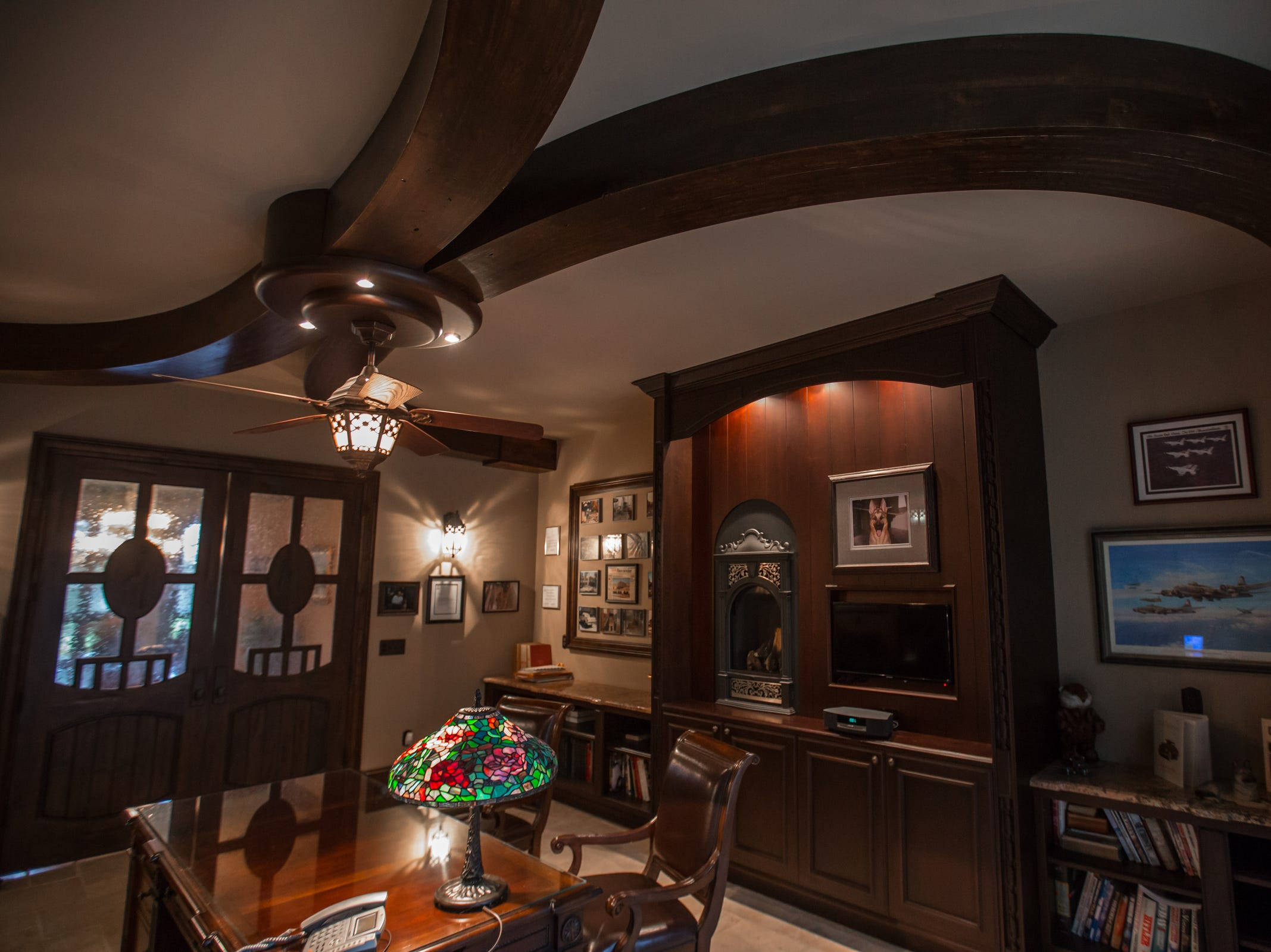 Custom doors and a unique library ceiling with radius curved beam work and custom formed lighting pendant are seen in the home envisioned after the Biltmore Estate designed by Alex Bogarts and built by an award winning builder as his own personal residence.