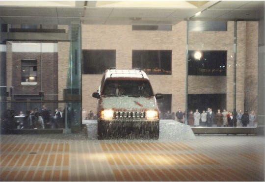 A 1992 Jeep Grand Cherokee crashes through a pane of glass during the North American International Auto Show at Cobo.