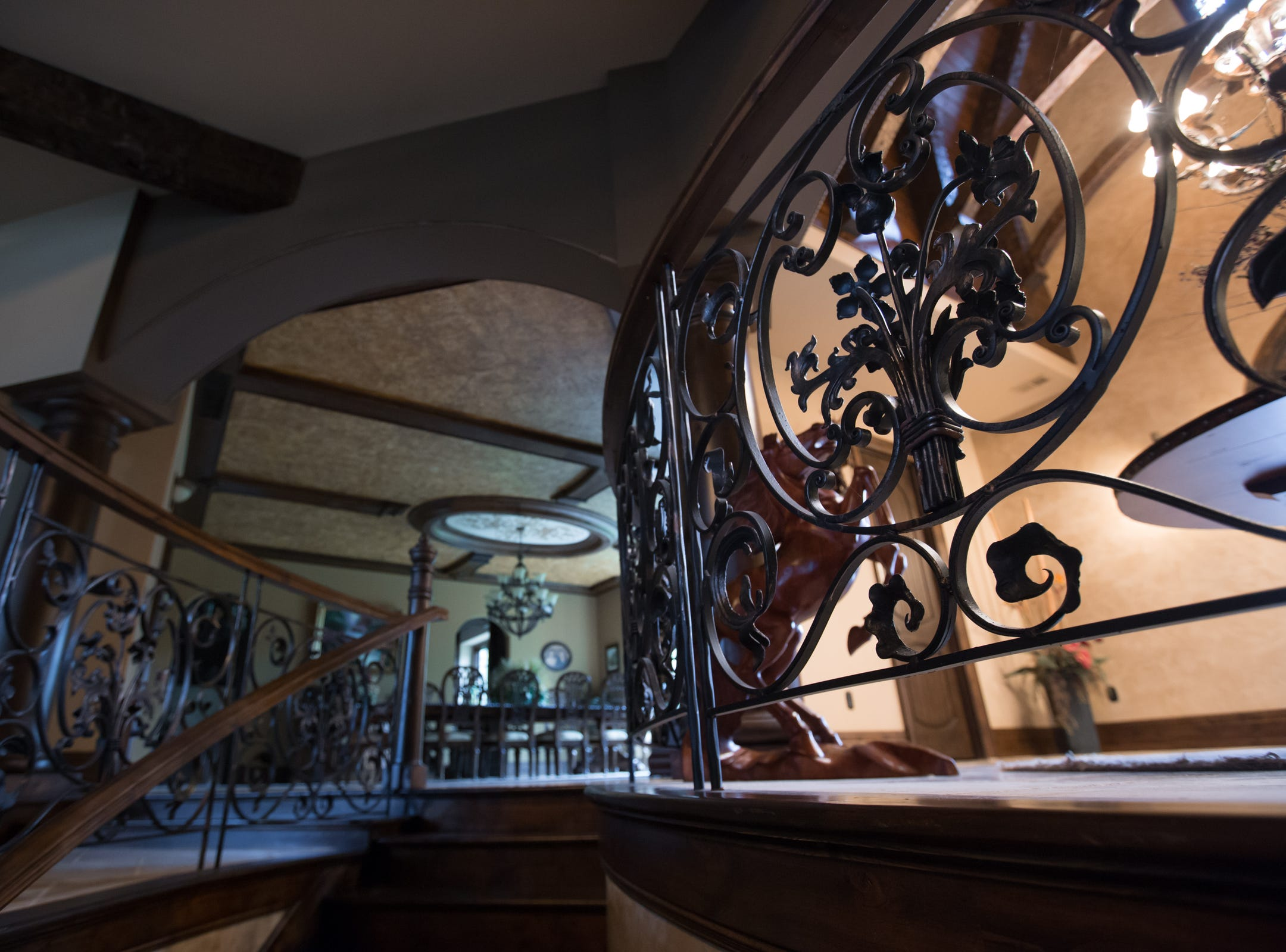 Hand forged wrought iron and alder wood staircase leading view from the basement to the dining room.