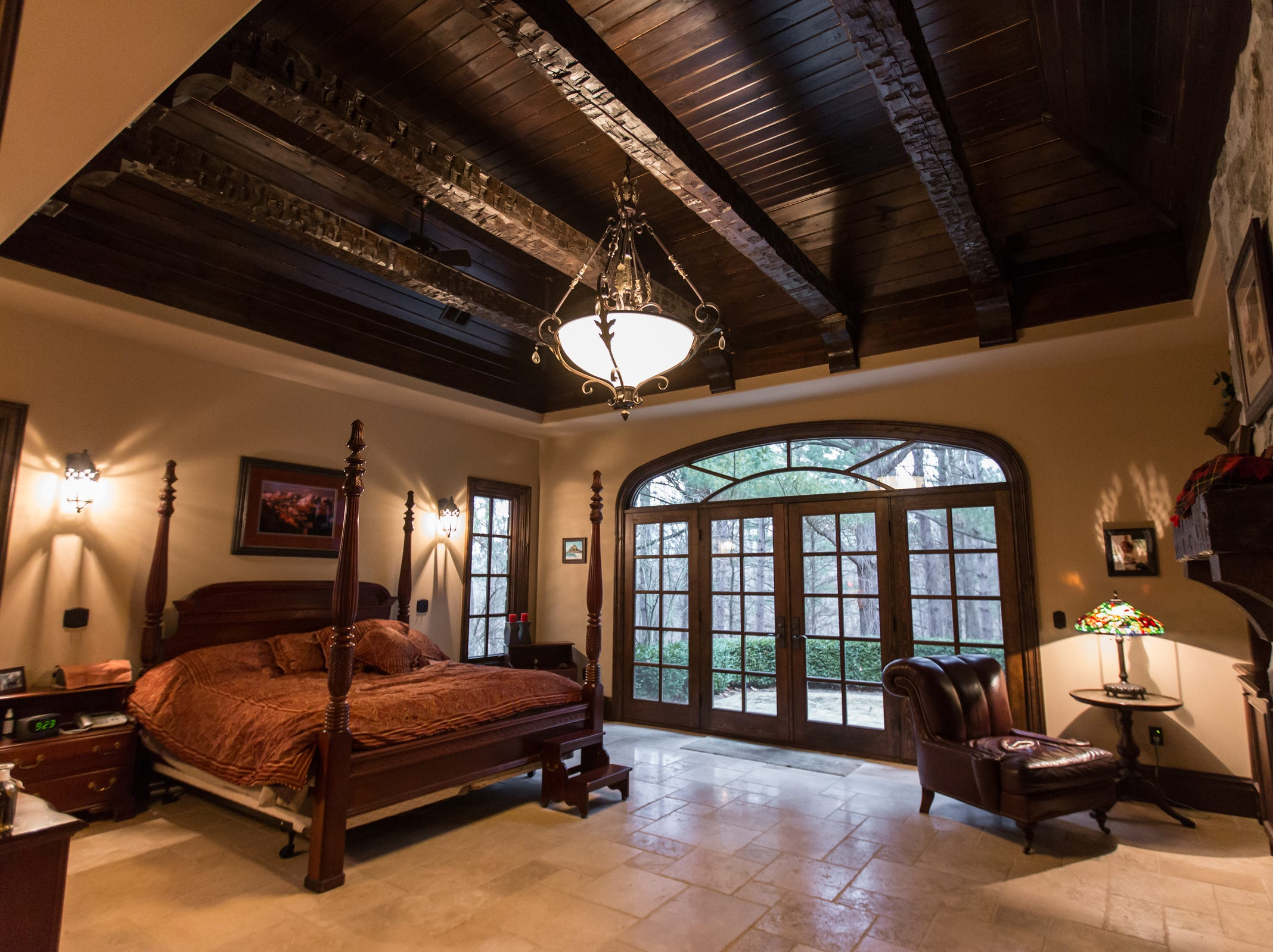 The distinctive ceiling in the owners' suite has a raised section of alder around rough-hewn Amish beams. The door wall is one of three places that group four French doors under an elliptical transom.